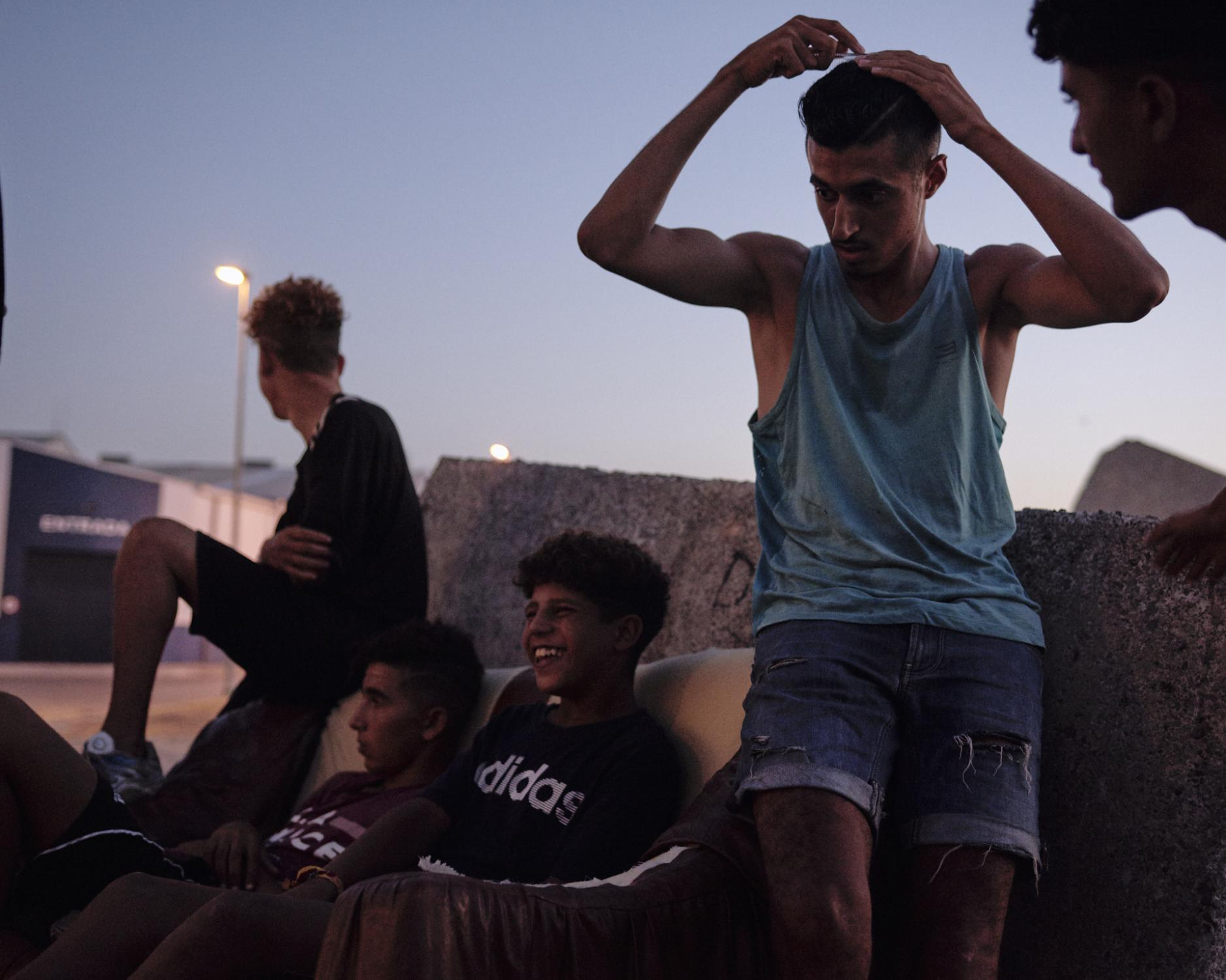 A group of MENA (Menores no Acompañados or Unaccompanied Minors), awaits the rest of their friends before the night comes. Kids are dispersed during the day over the town of Ceuta, begging money or trying to get some gigs. Very occasionally, organizations look for these kids to see if they need medical assistance, food, or clothes. Ceuta, Spain, 2019.