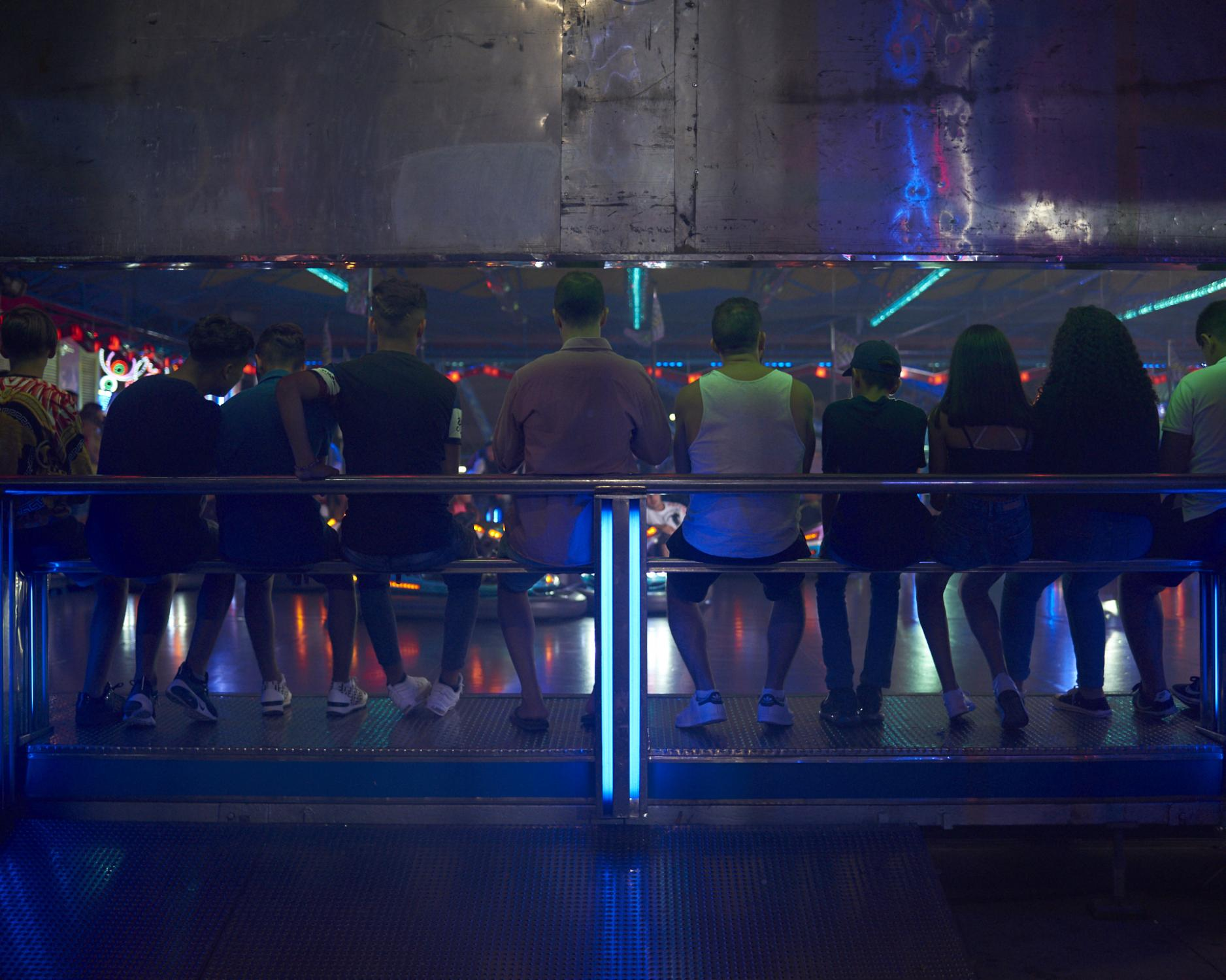 A group of teenagers hangs waiting for their turn on the bumper cars. Ceuta, Spain, 2019.