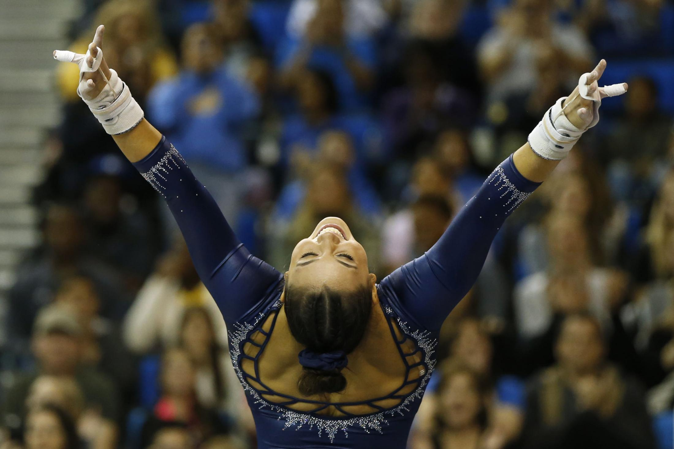 LOS ANGELES, CALIFORNIA - MARCH 10:  Kyla Ross dismounts from her uneven parallel bars routine during a meet against Stanford at Pauley Pavilion on March 10, 2019 in Los Angeles, California. (Photo by Katharine Lotze/Getty Images)