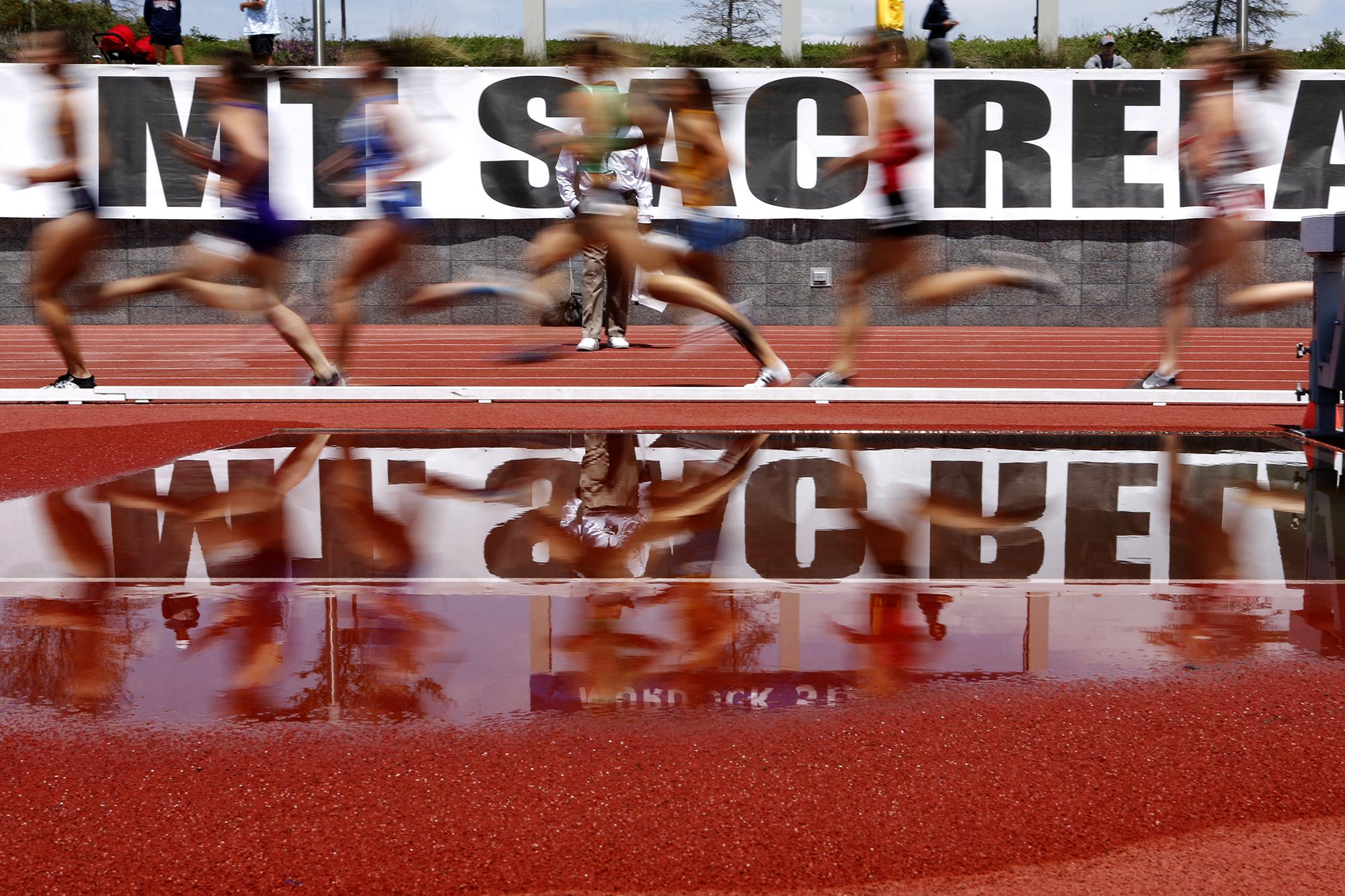 TORRANCE, CALIFORNIA - APRIL 19: Runners are seen reflected in the water obstacle for the steeplechase as they compete in the collegiate women's section of the 1500 meter run on the first day of the 61st Mt. SAC Relays at Murdock Stadium at El Camino College on April 19, 2019 in Torrance, California. (Photo by Katharine Lotze/Getty Images)