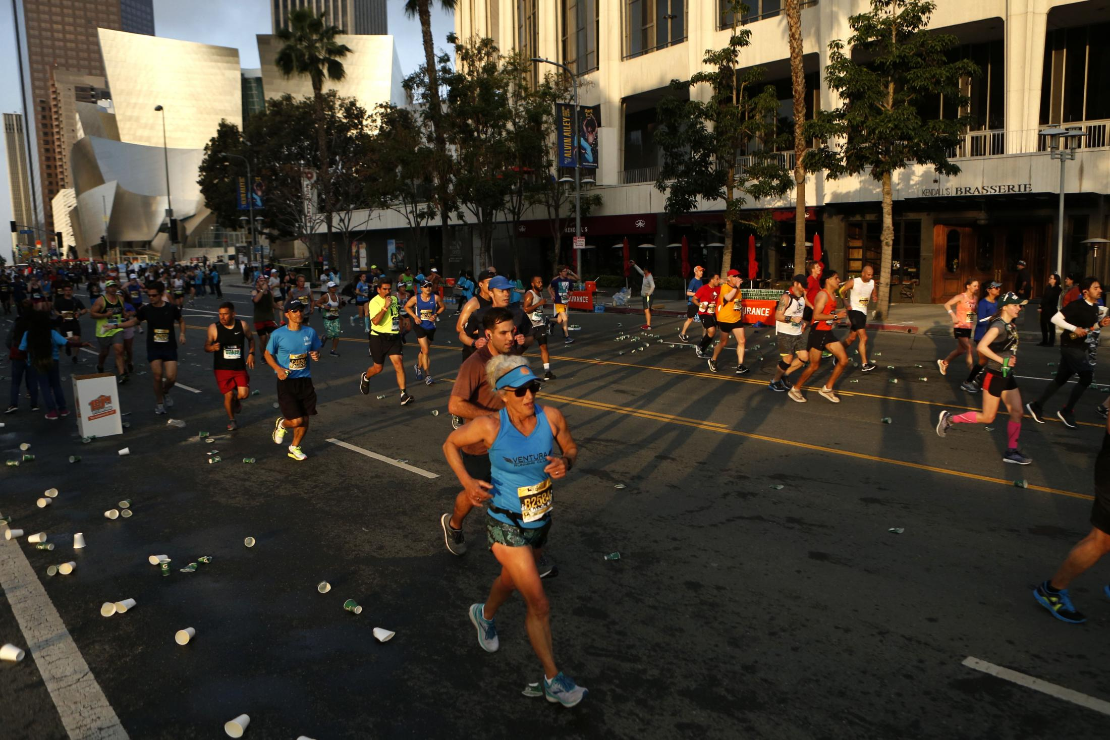 LOS ANGELES, CALIFORNIA - MARCH 24:   Runners make their way down Grand Avenue during the 2019 Skechers Performance Los Angeles Marathon on March 24, 2019 in Los Angeles, California. The race, run annually in March, takes runners from Dodger Stadium near downtown Los Angeles, through Hollywood and Beverly Hills to Santa Monica, passing many LA landmarks along the way. (Photo by Katharine Lotze/Getty Images)