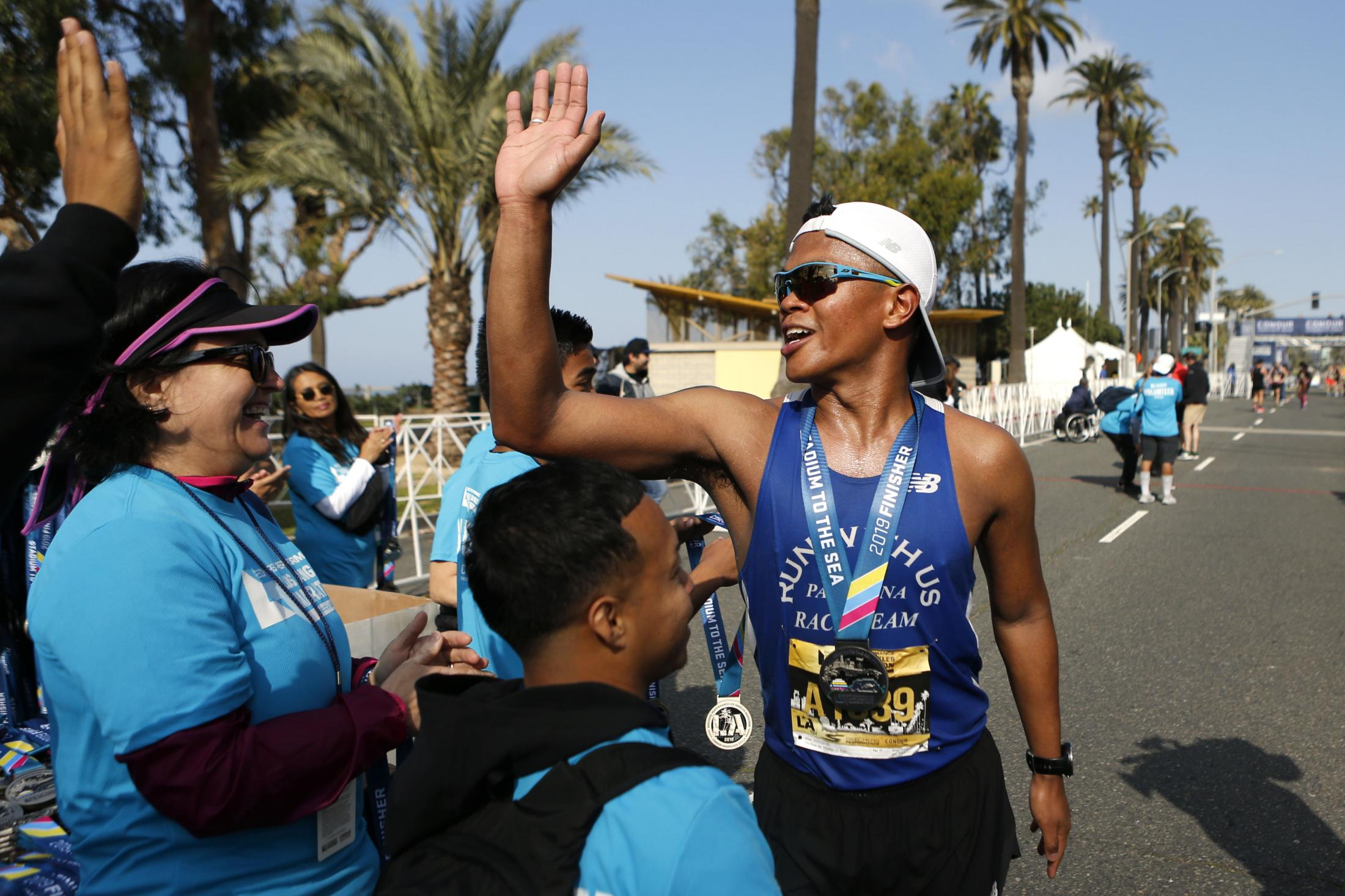 LOS ANGELES, CALIFORNIA - MARCH 24:  A runner high-fives volunteers after finishing the 2019 Skechers Performance Los Angeles Marathon on March 24, 2019 in Los Angeles, California. (Photo by Katharine Lotze/Getty Images)
