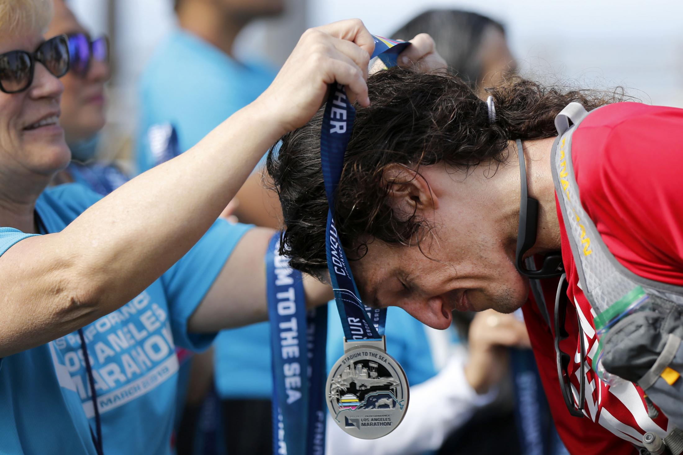 LOS ANGELES, CALIFORNIA - MARCH 24:  A runner accepts a medal for finishing the 2019 Skechers Performance Los Angeles Marathon on March 24, 2019 in Los Angeles, California. (Photo by Katharine Lotze/Getty Images)
