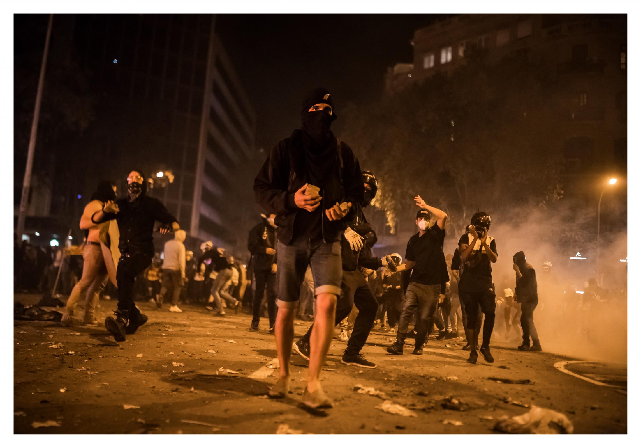 """The protesters come forward with stones in their hands chanted slogans such as """"Out with the forces of occupation"""" """"October 1st, neither forget nor forgive"""", """"You fascists are the terrorists"""" and """"Antifascist Catalonia"""". S imultaneous fires in the center of Barcelona during the altercations. October 2019, Barcelona, Spain."""