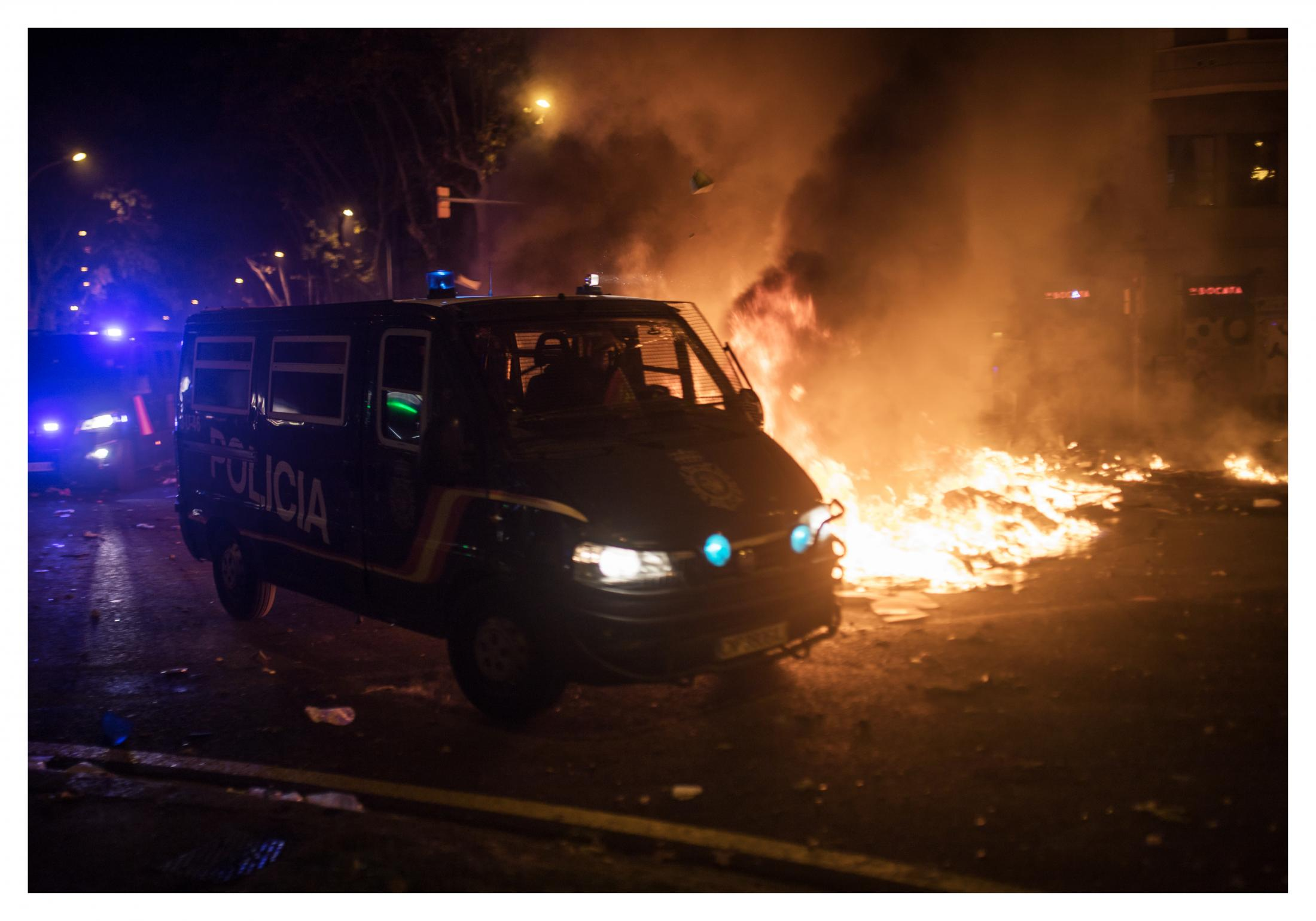 Barcelona, Spain. Police vans race down the street through barricades. The police force protesters into Plaça Urquinaona and then disperse them further protesters can be seen running away down the side streets. A climate of confusion was created because the tension then moved to the streets of the Eixample on which traffic was circulating. October 2019, Barcelona, Spain.