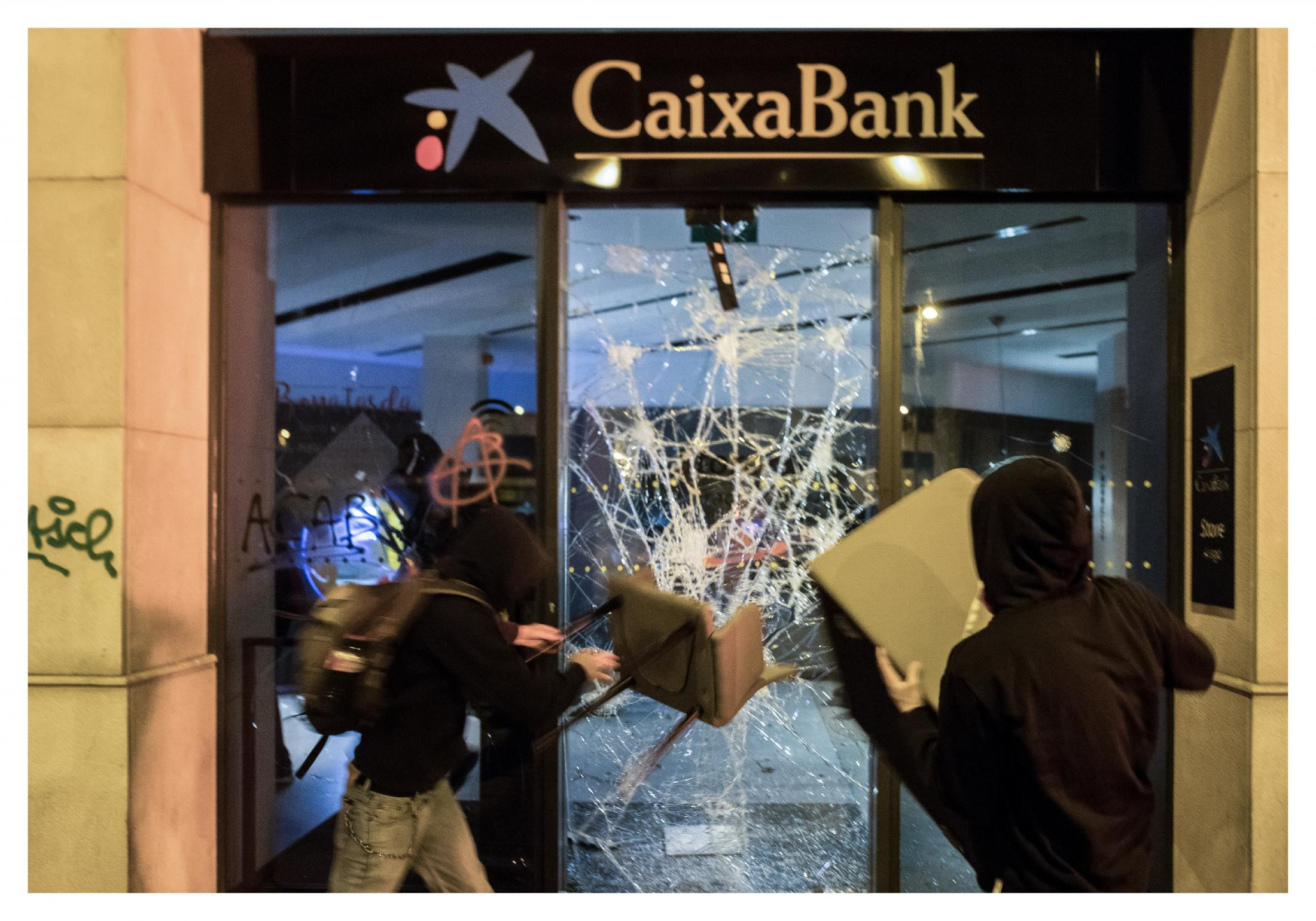 """Businessmen warn about the risk of """"destruction"""" of the Catalan economy. The economic sector shows its concern about the impact on business activity and asks for dialogue to resolve the conflict . Hooded protesters break the Caixa Bank windows with chairs and achieve other specific actions. It is not Tsunami's intention was declared to become a new element offering opinions on the news. October 2019, Barcelona, Spain."""