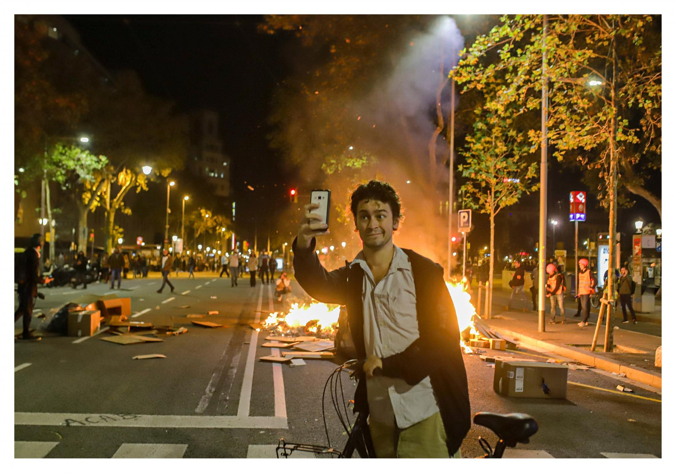 A young man takes a selfie while the center of Barcelona was tense, at various points of Passeig de Gràcia, Pau Claris and Diagonal because of police actions to deal with the burning of some containers and the creation of barricades to contain the police advance. The riots in Barcelona have left significant damage to street furniture. Fomento Ministry has put them at 7 million euros. October 2019, Barcelona, Spain.
