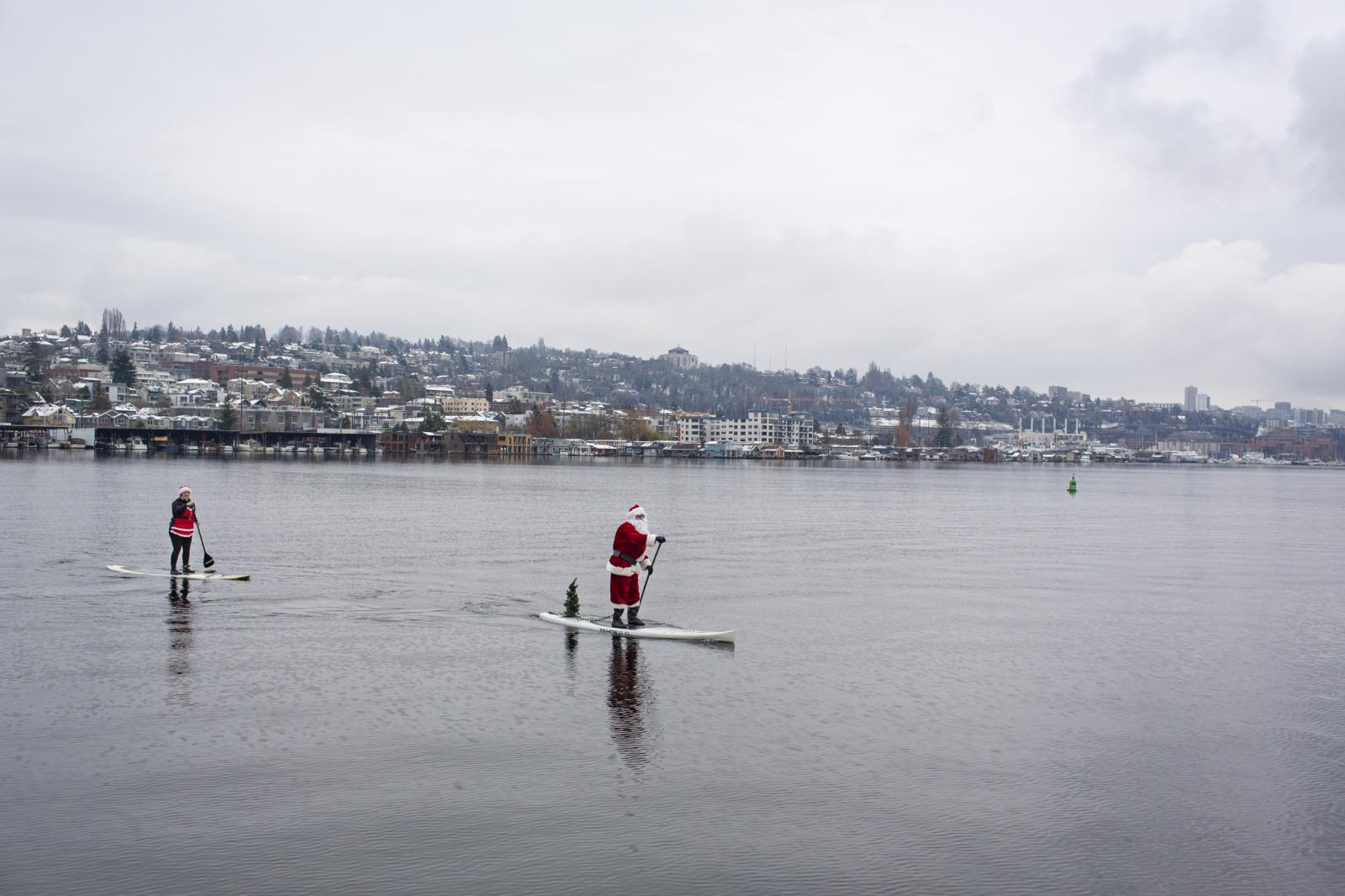 Paddleboard riders dressed as Santa Claus pass Gas Works park at Lake Union in Seattle on Dec. 25, 2017.