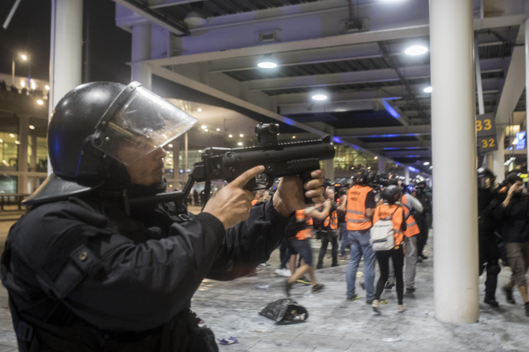 """Riot squads act against protesters at the airport in Barcelona. In 2014 a ban on the use of rubber bullets as an anti-riot weapon was imposed on the Catalan police force following a high profile campaign led by victims who had lost vision. Then Mossos de Esquadra only used """"foam"""" bullet to control the altercations recorded in the Catalan streets, while for National police and Guardia Civile It was still possible to use rubber bullets because of """"a scale of order"""" and the rules that allow using this riot gear """"are above"""" what is established in the Catalan law. October 2019, Barcelona, Spain."""