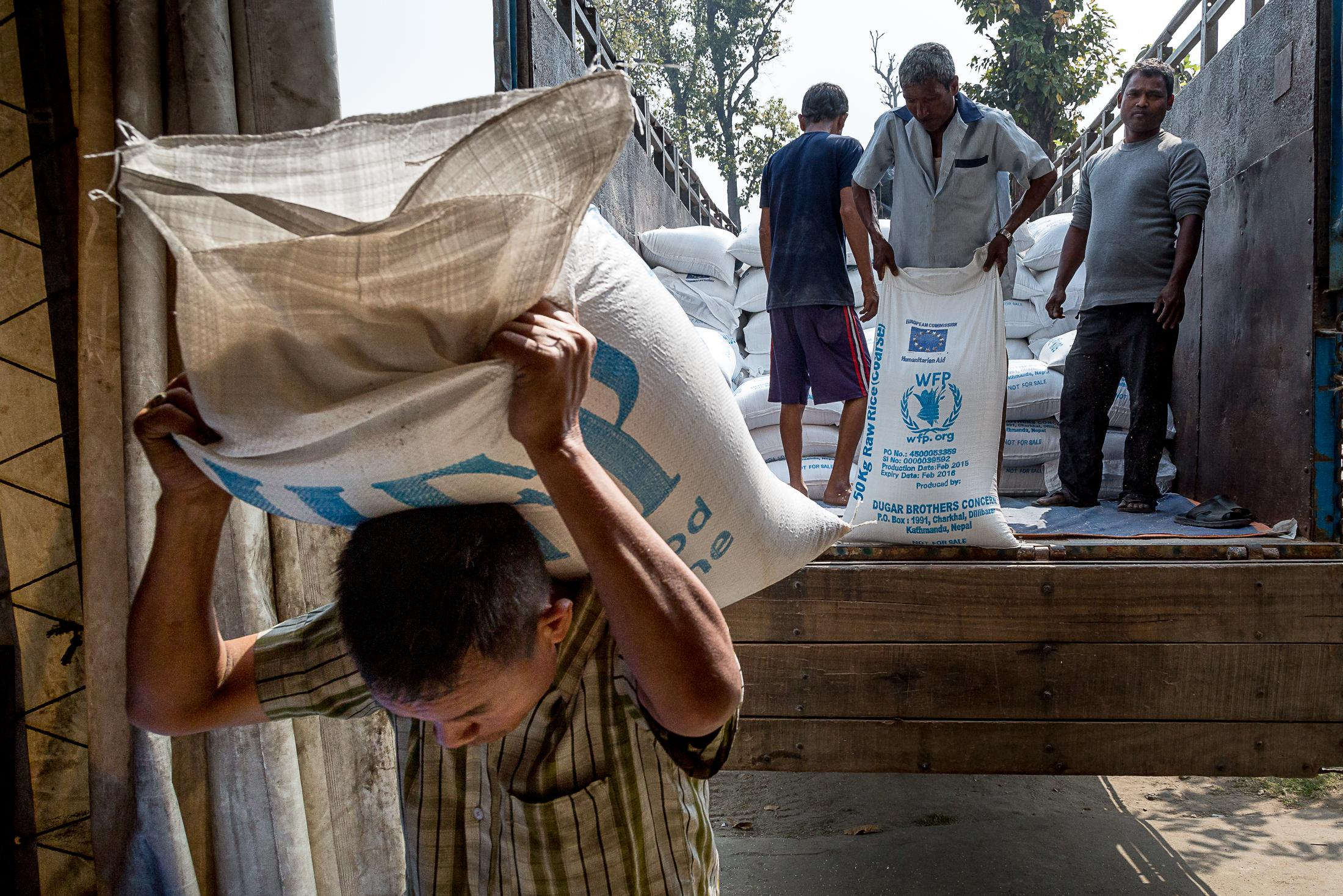 BELDANGI, NEPAL - MARCH 13: A worker carries a sack filled with rice inside one of the World Food Programme rice storage wards in the Beldangi 2 refugee camp on March 13, 2015 in Beldangi, Nepal. Photo: © Omar Havana / Getty Images