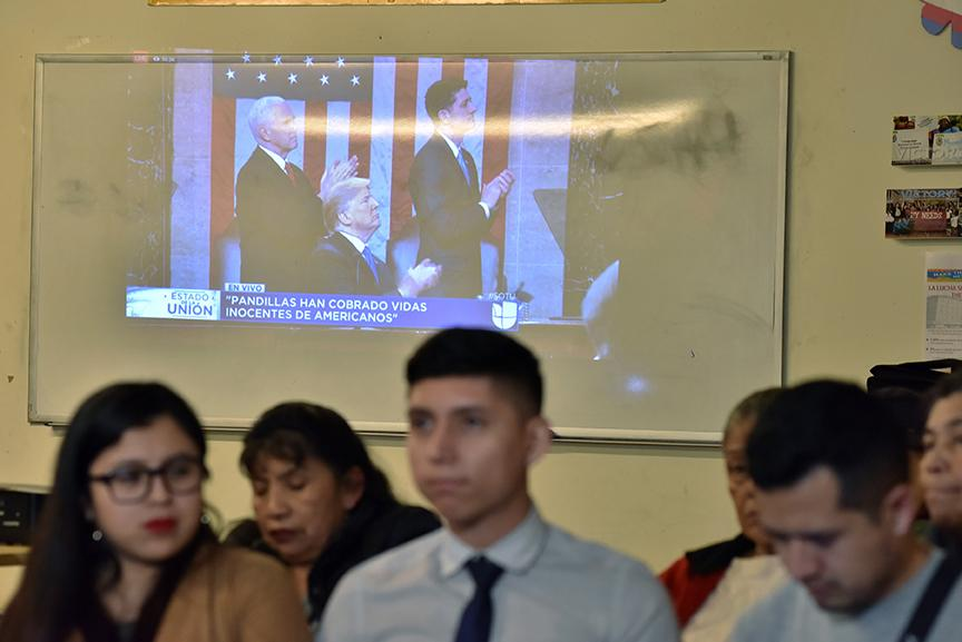 DACA recipients and Dreamers Yatziri Tovar,25 student of Political Sciences at City College (left) and Anthony Alarcon student of Studies Film (center)  turn their backs on U.S President Donald Trump on-screen during the State of Union speech at the pro-immigrant headquarters 'Make The Road New York' in Jackson Heights, Queens,on January 30, 2018 in New York City.