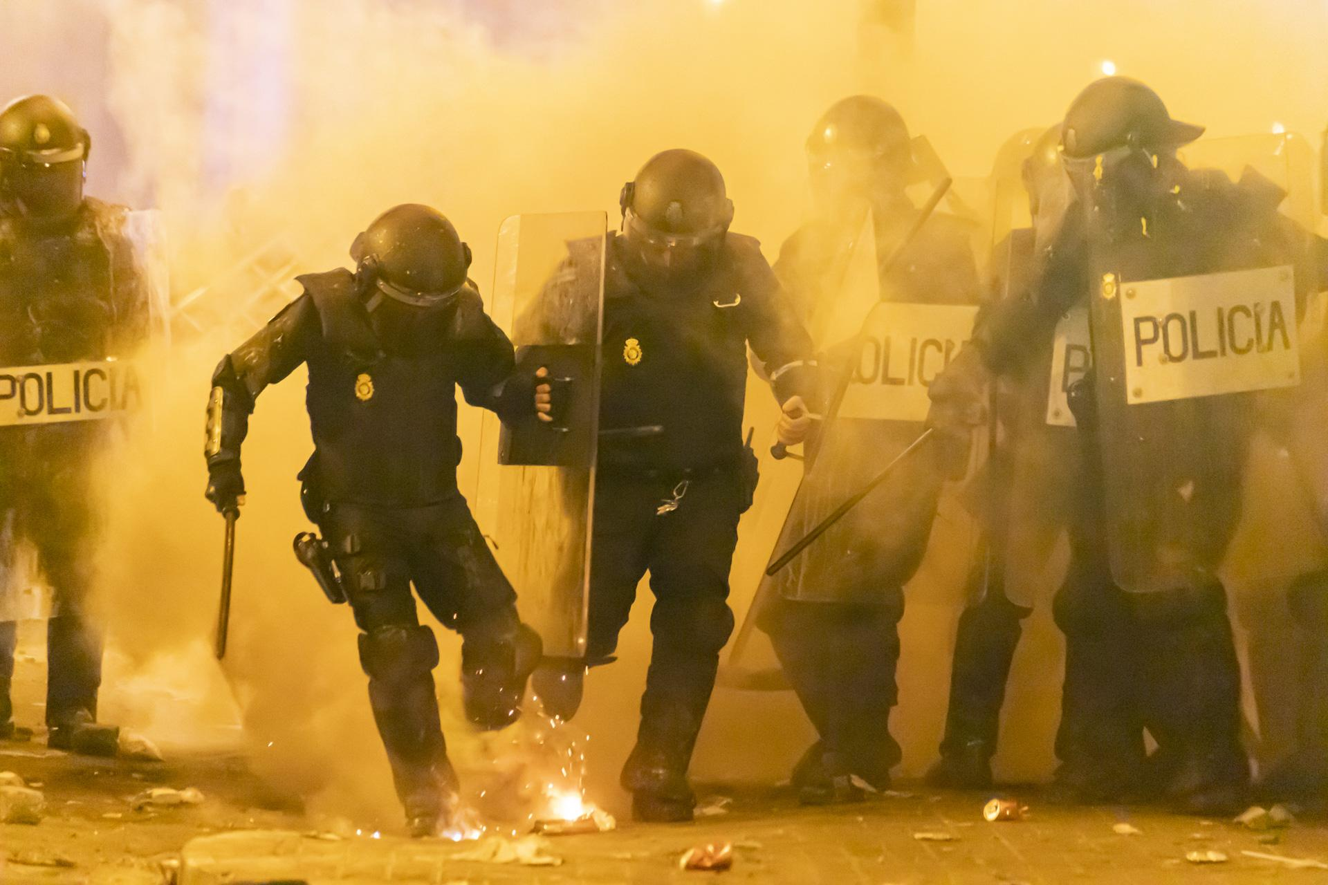 A row of riot police receives firecrackers and smoke bombs while the anti-riot teams tried to break up groups of protesters who had originated protests outside the Spanish National Police station and continued inUrquinaona square . October 2019, Barcelona, Spain.