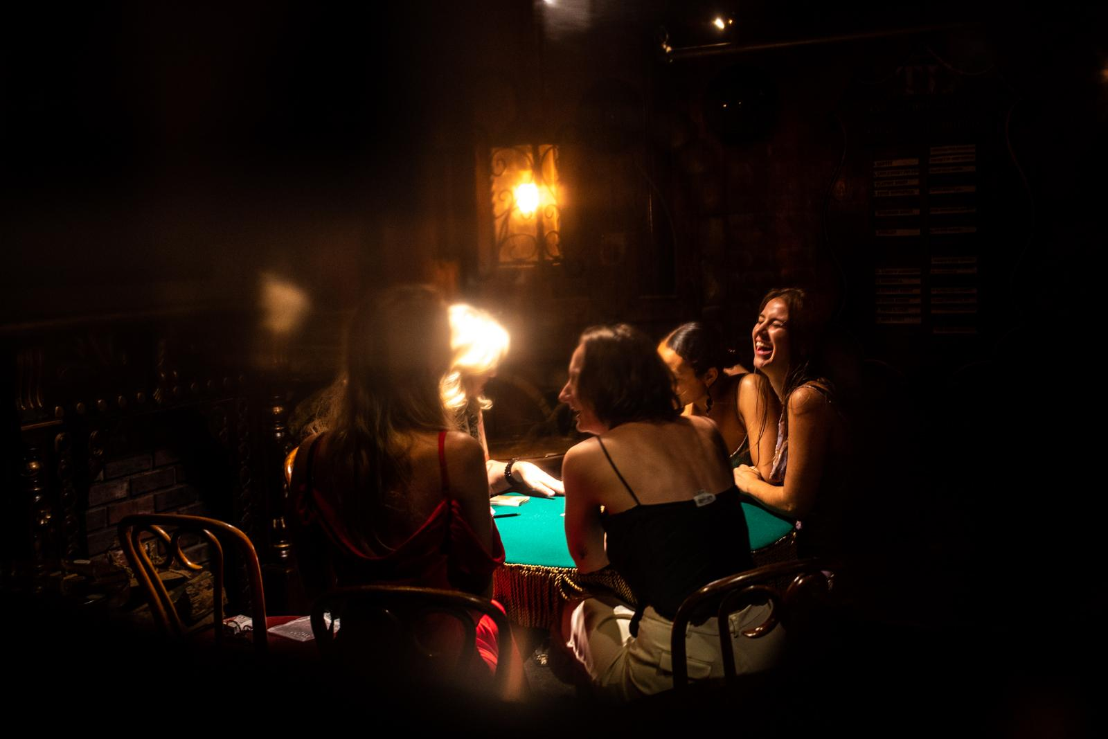 Breeanin Hansteen, Sasha Rieders, Micaela Morton and Magdalena Rieders watch Cydney Kaplan, 45, while she performs a card trick at the Magic Castle in Hollywood.