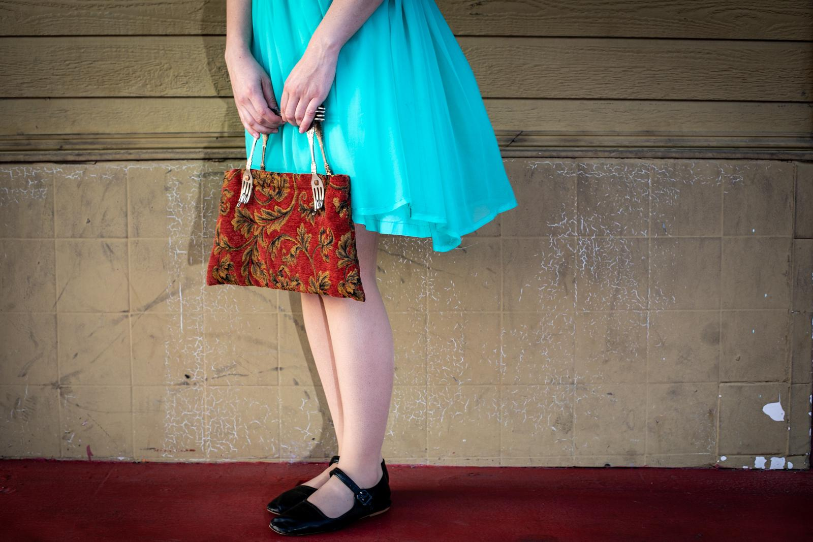Elizabeth Messick, 29, stands with her magic purse in an alley in Los Angeles Chinatown.