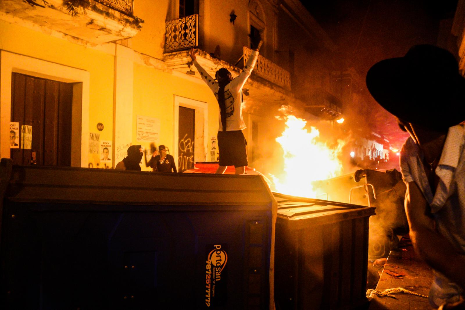 Demonstrators set fire to trashcans during clashes with riot police.