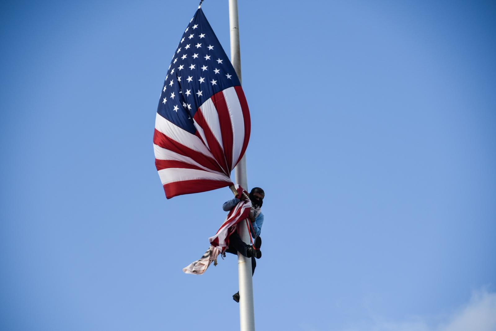 Tito Kayak, environmental activist, takes down the US flag on the outsides of the Capitol of Puerto Rico.