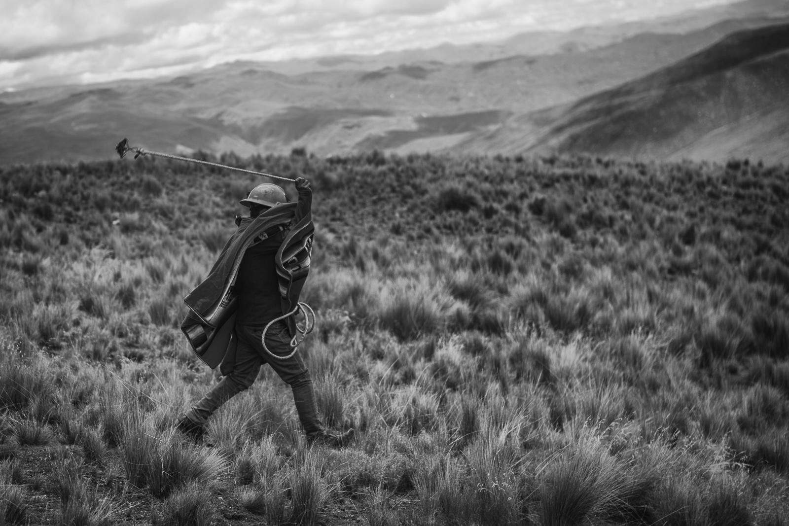 Man running with a slingshot or huaraca. The ritual is sacred to the people in Canas. The victor communities will ensure a thriving year for their farming activities.