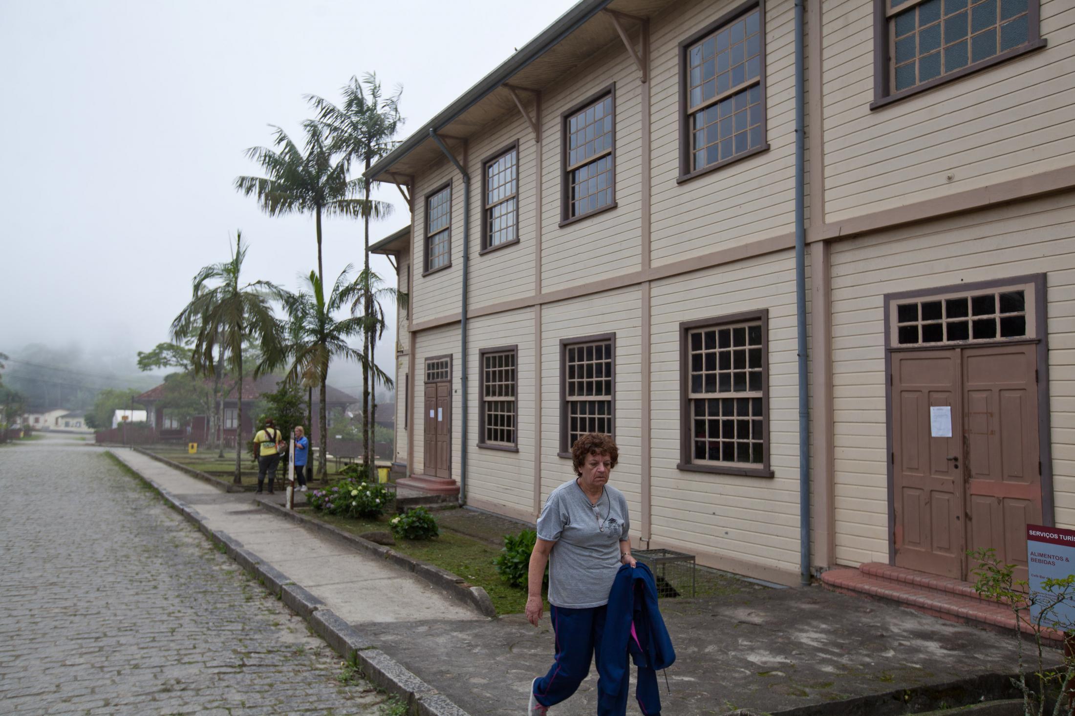 Mulher caminha ao lado da sede do clube União Lira-Serrano, ponto de encontro dos moradores da vila. Woman walks next to the clubhouse Union Lira-Serrano, a meeting point of the villagers.
