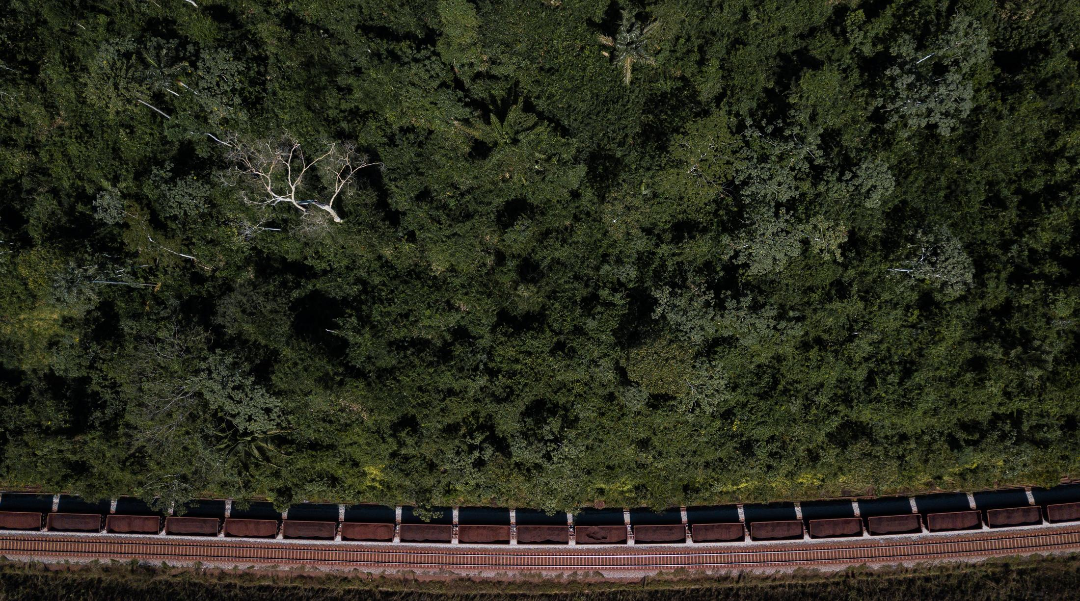"""A train from the mining company, Vale, cuts through the forest with its hundred iron-laden wagons extracted from the Amazon. This picture is part of a long-term project (in progress) a documentary and artistic exploration that seeks to research, witness and document an important issue in times of climate change: the relationship of society with its geography, """"Stress Nexus - Latin America and Caribe Chapter"""" . Parauapebas, Para, Brazil. 2019, July 05."""