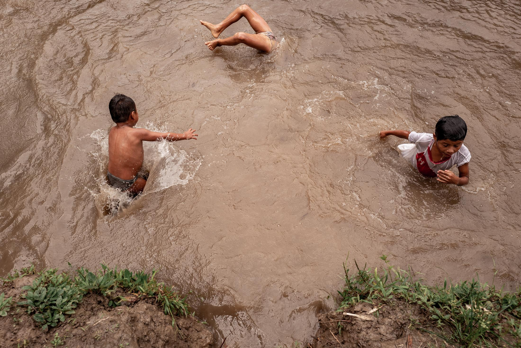 Children of the Wampís ethnic group play in the waters of the Amazon.