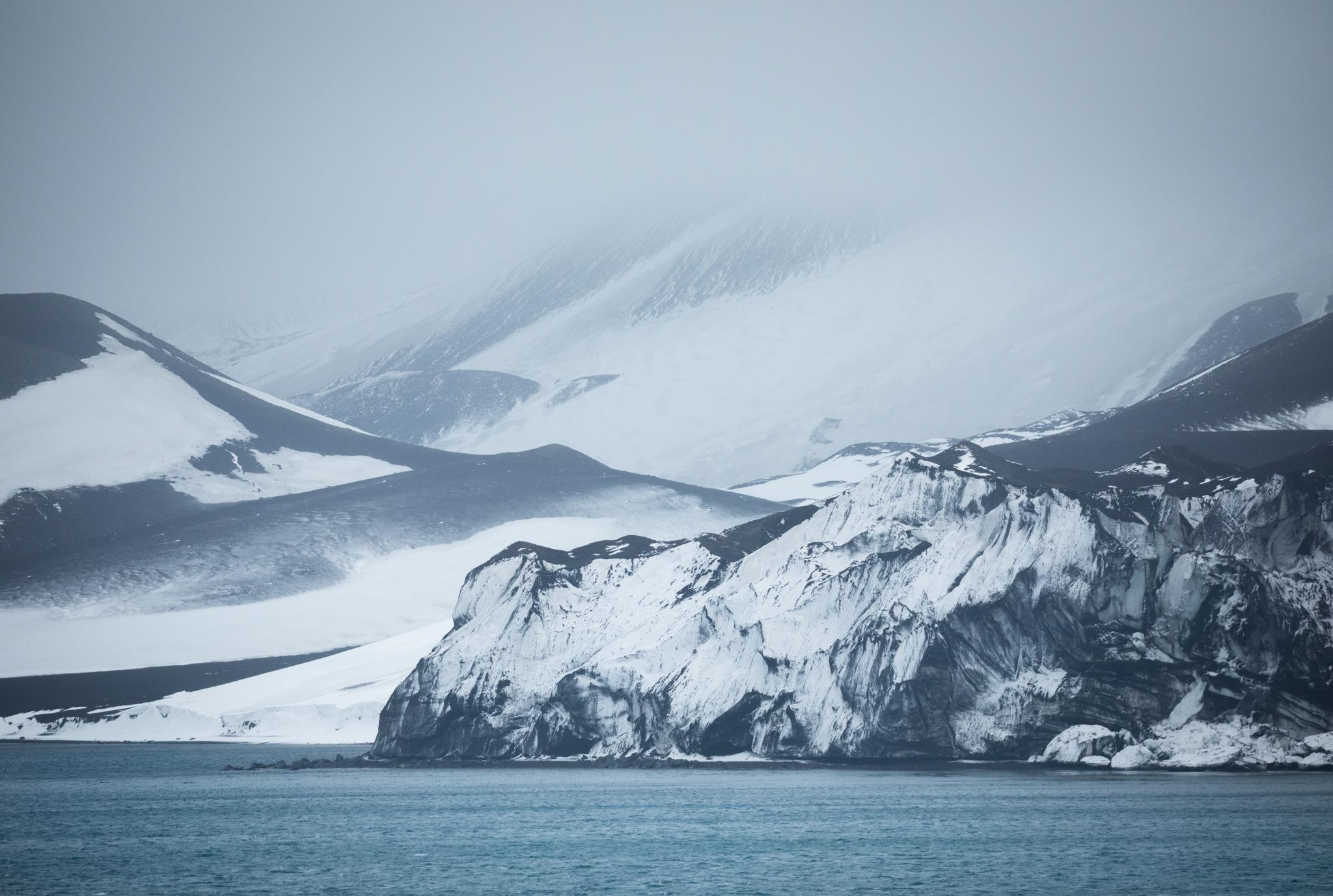 The glaciated inner coastline of Deception Island, blackened by volcanic ash - a striking interaction of fire and ice.