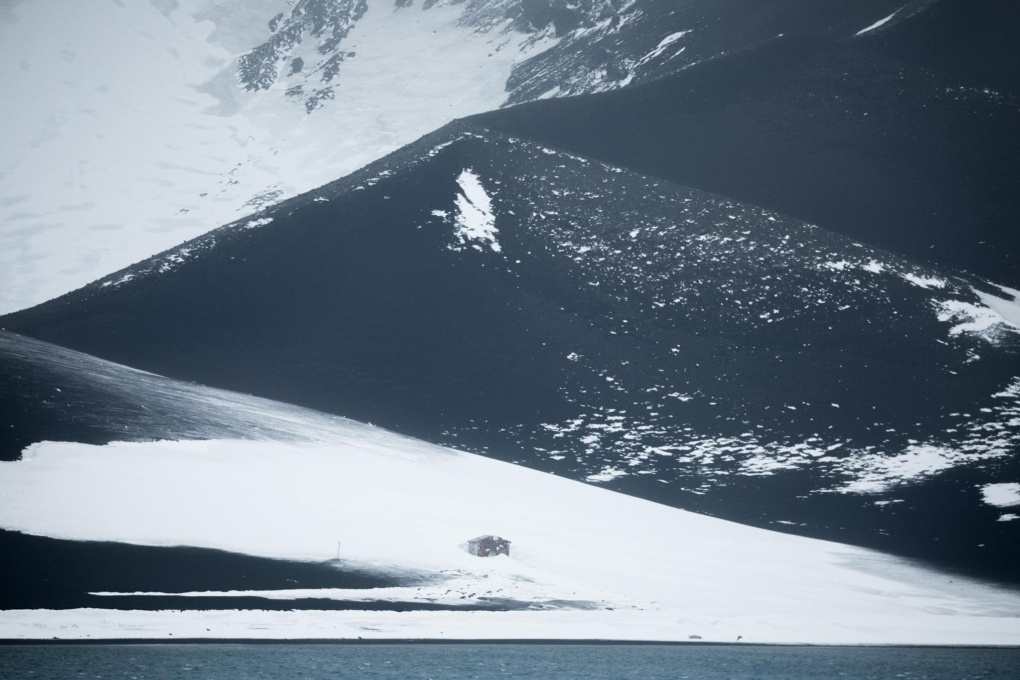 A derelict hut stands alone on a dramatic slope of snow and ash, deep inside the Deception Island caldera. It lies about 1 km south of Pendulum Cove, where the remains of the Chilean Presidente Pedro Aguirre Cerda Station (destroyed by volcanic activity in the late 1960s) are located.