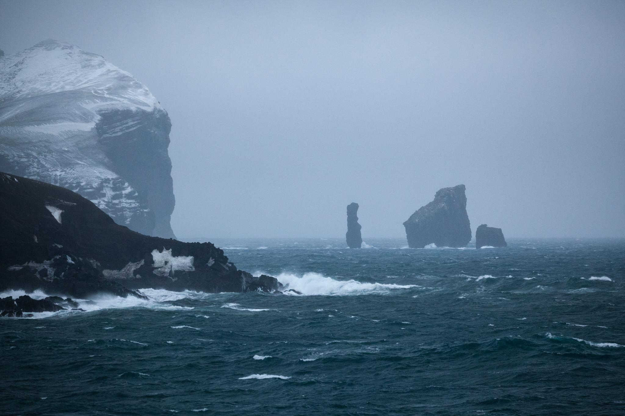 The rock formation known as the Sewing-Machine Needles, visible from miles away by ship, marks the general area of the entrance to the Deception Island Caldera.