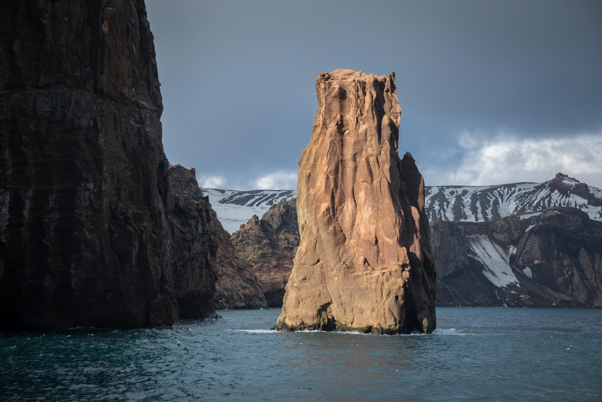 A rock formation marking the eastern side of Neptune's Bellows, the narrow passage into the Deception Island caldera. Ships entering must take care to sail close to the coastline, as a submerged rock known as Ravn Rock lies directly in the center of the passage.