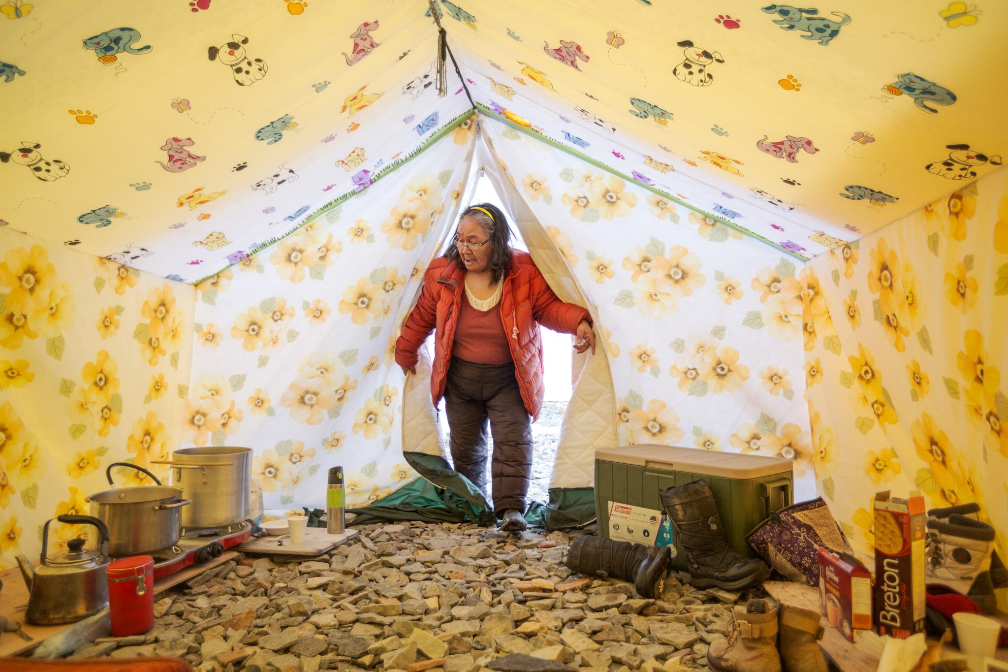 Tootalik Ejangiaq enters her tent at the annual spring camp where she helps young people learn traditional Inuit skills.