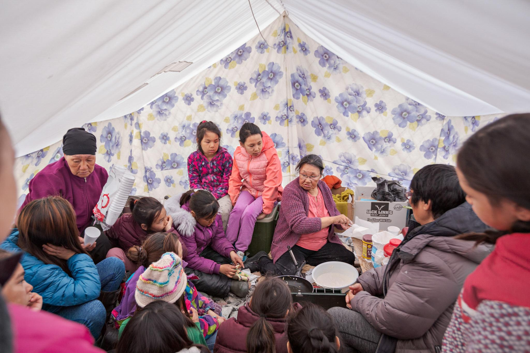 Tagoonak Qavavauq, an Inuit elder, teaches children how to make a bread called bannock on a school field trip. Ancestral knowledge about how to survive on the frigid land is disappearing with the elders. Many are determined to pass down traditions, particularly to children whose families no longer hunt or go camping. Learning how to live with limited resources is key to survival at a time when food insecurity and poor nutrition are increasing problems in Inuit communities.