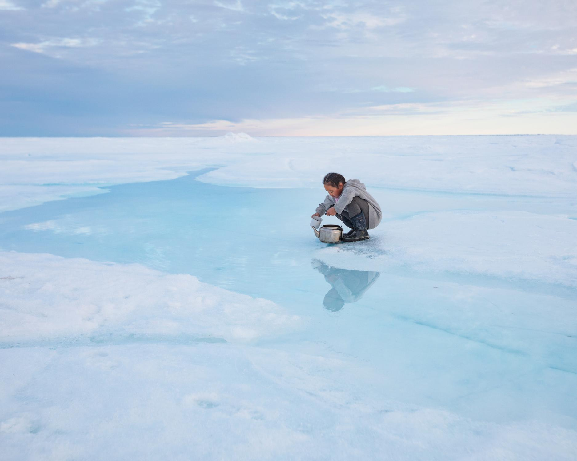 When sea ice ages, the salt sinks into the ocean, leaving fresh, drinkable water on top. Charlotte Naqitaqvik collects a teapot of water at her family's hunting camp in Nuvukutaak, near the community of Arctic Bay in northern Canada.