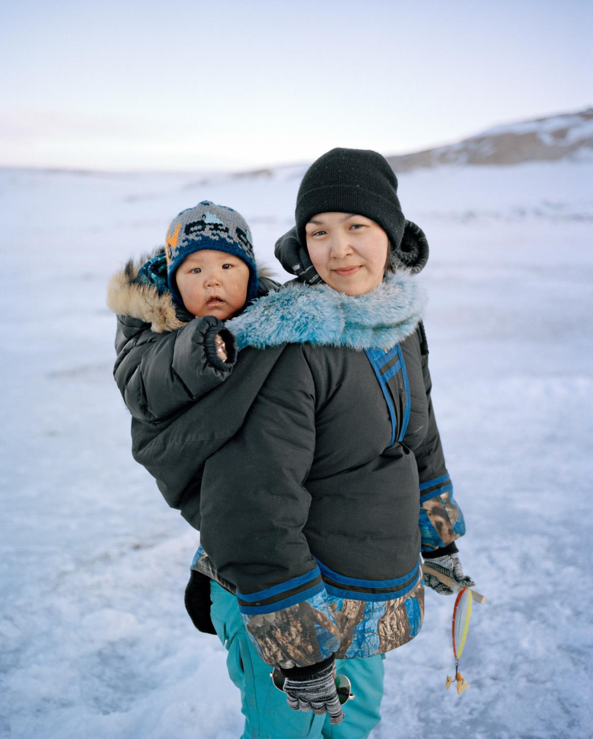 Swaddled in an  amauti— a parka with a built-in baby carrier—Spencer joins his mother, Clara Itturiligaq, on a fishing trip.