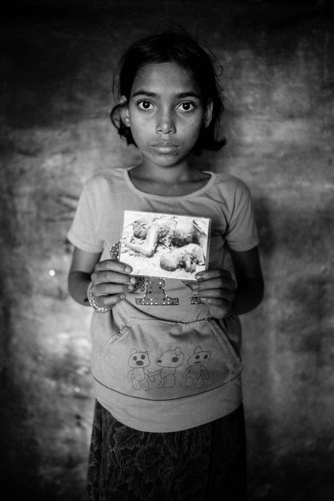 Ajda Bibi, 10 from Fokhali village, Maungdaw township in Myanmar.  The Myanmar soldiers shot her father and little sister in the head and Ajda doesn't know what happened to her mother. Those that fled the village were shot at by the military and Adja suffers from shrapnel wounds on her leg. The photo she holds in the portrait was given to Ajda by a neighbor who returned to Fokhali after the attack and took cell phone photos. The photographer told her the image depicts Aida's father and younger sister in front of her former home.