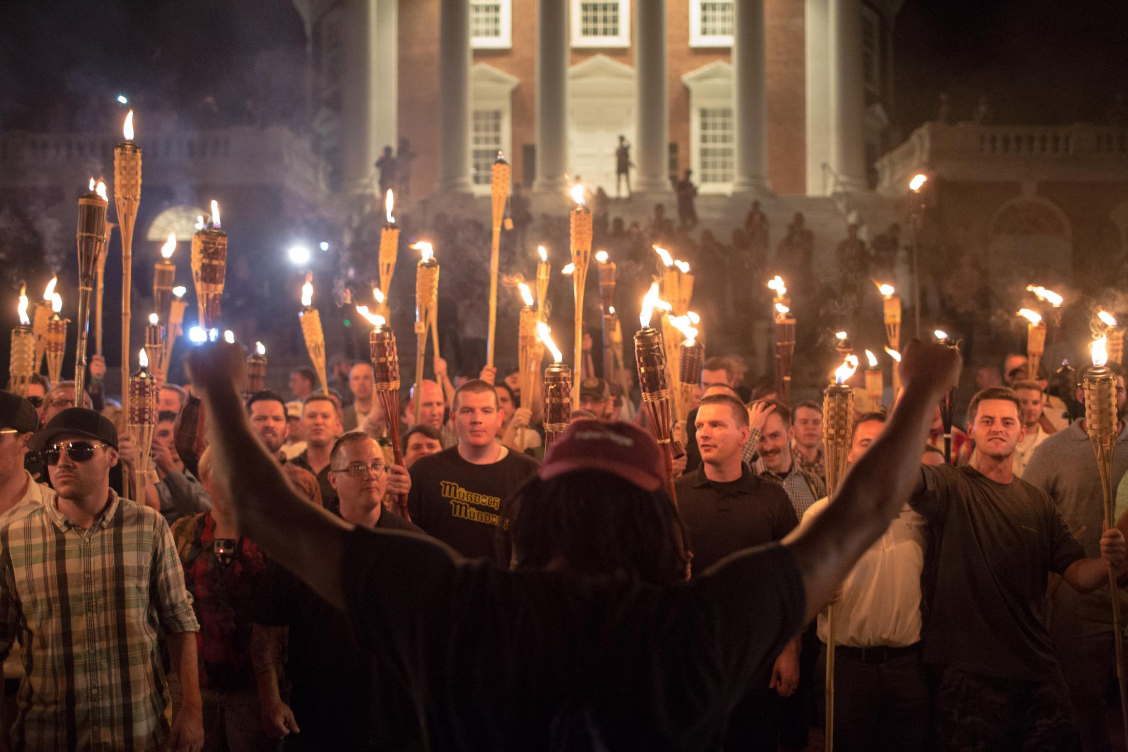 A counter-protester holds up his hands in front of hundreds of white nationalist protesters with torches at the Thomas Jefferson Memorial statue on the campus of the University of Virginia in Charlottesville, VA on August 11, 2017.