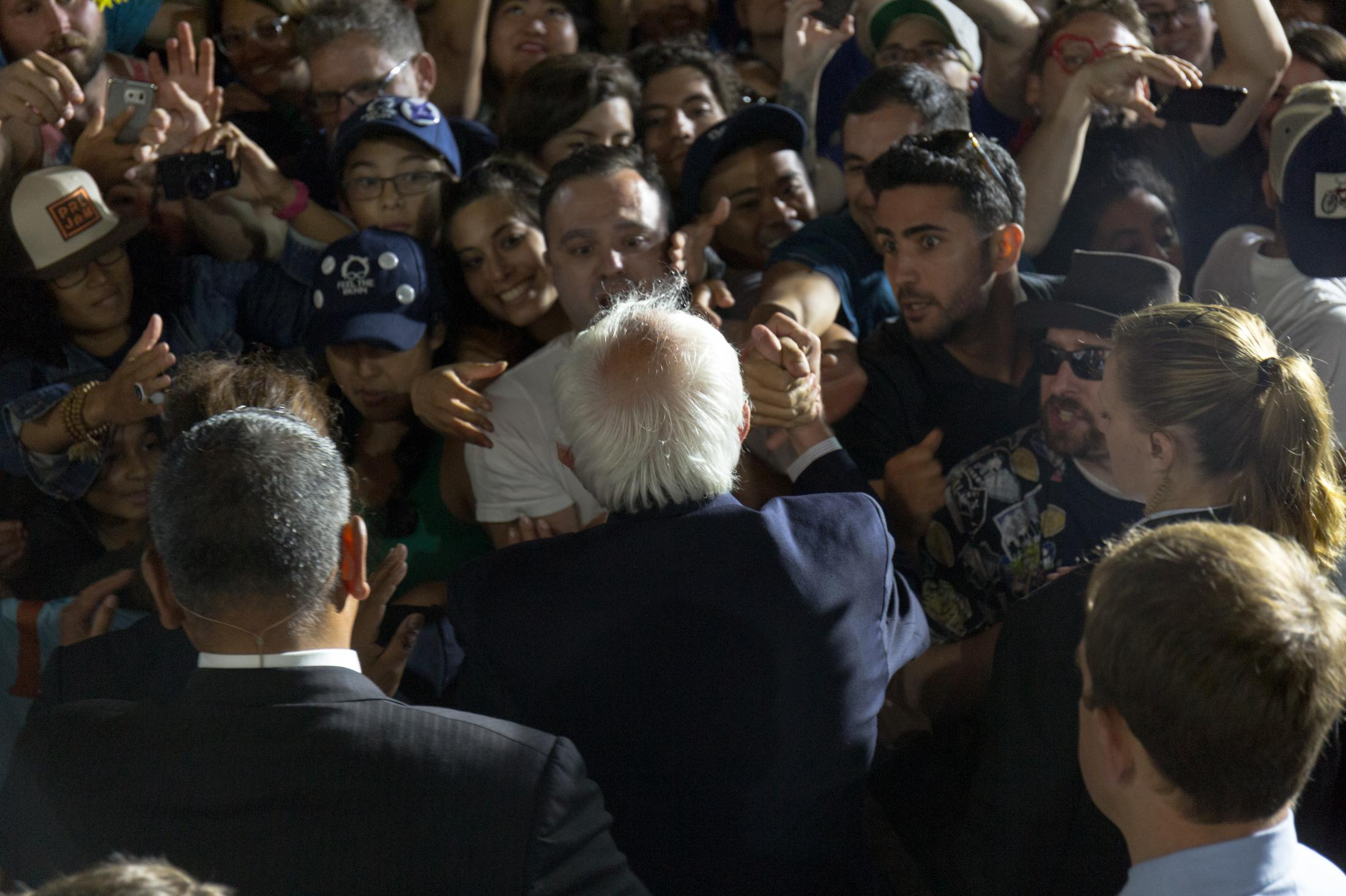 Vermont Senator Bernie Sanders shakes hands as he walks along the crowd of supporters after his speech at the Los Angeles Memorial Coliseum on June 4, 2016.