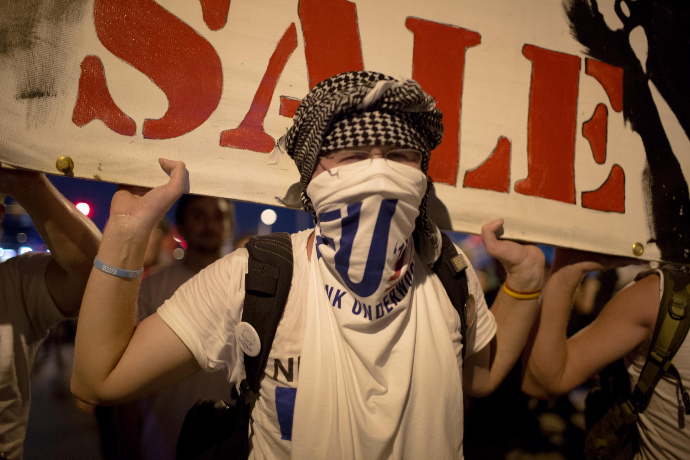 "A protester carrying a sign for Bernie Sanders that says ""not for sale"" marches towards the Wells Fargo Center in Philadelphia, PA during the Democratic National Convention on July 26, 2016."