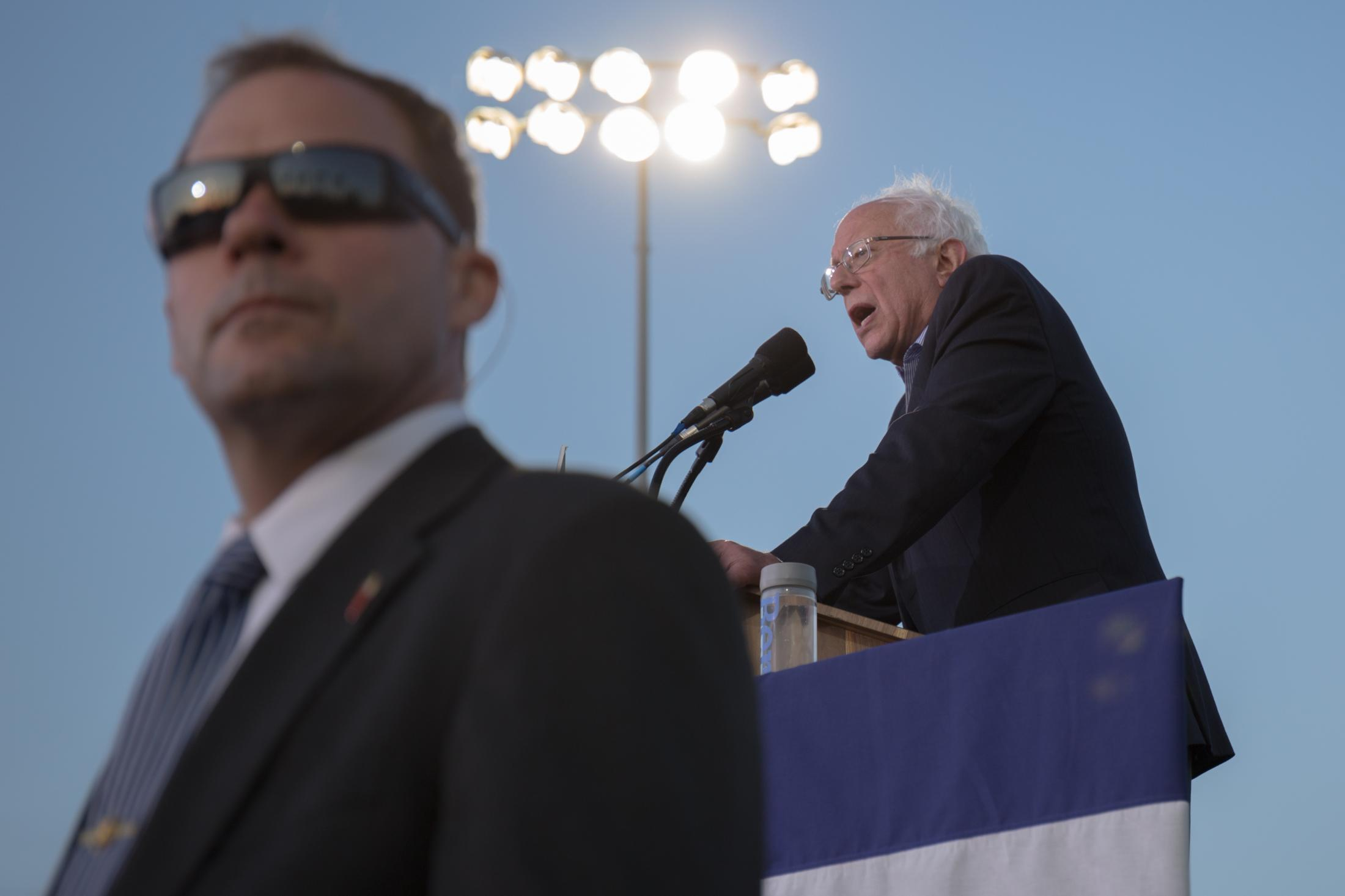 Vermont Senator Bernie Sanders gives a speech while a member of the Secret Service watches the crowd around him at Santa Monica High School on May 23, 2016.