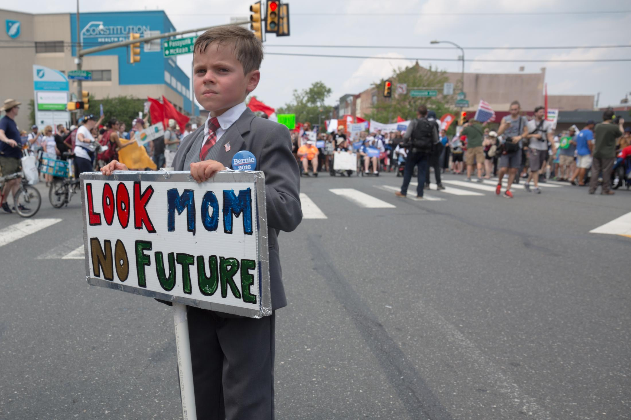 A boy in a suit holds a sign during a march on Broad Street in towards the Wells Fargo Center in Philadelphia, PA during the Democratic National Convention on July 26, 2016.