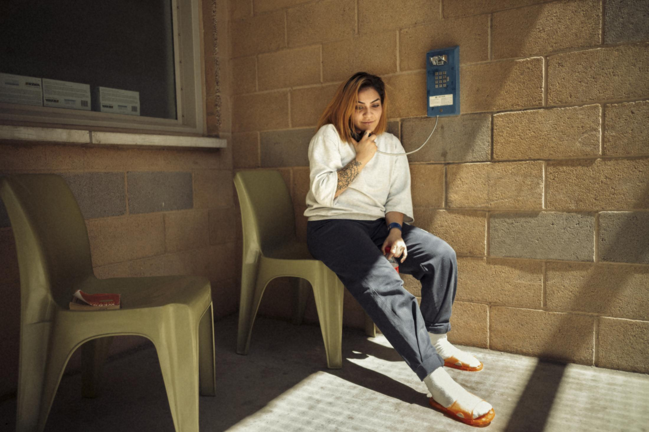 Laura Mejia speaks on the phone from the exercise yard in a high-level cell block of the Las Colinas correctional facility for women in San Diego, CA.