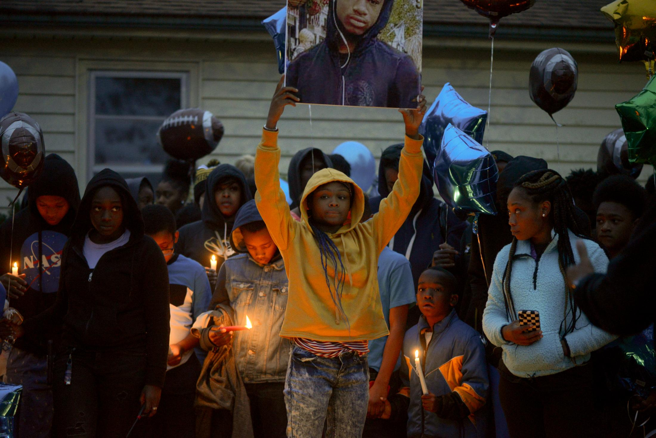 "Dajion Harris' sister DenayJah Harris holds up a sign with a photo of him during a vigil in Columbia on Thursday, Oct. 24, 2019. Dajion's football teammates gave him the nickname ""Mustard"" according to his obituary by H.T. May and Sons Funeral Home."