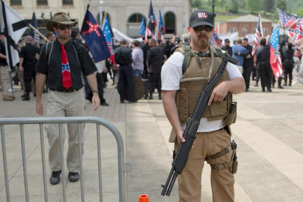 A man with a white supremacist group guards the entrance to the Nationalist Front rally with a shotgun in Pikeville, Kentucky on April 29, 2017.