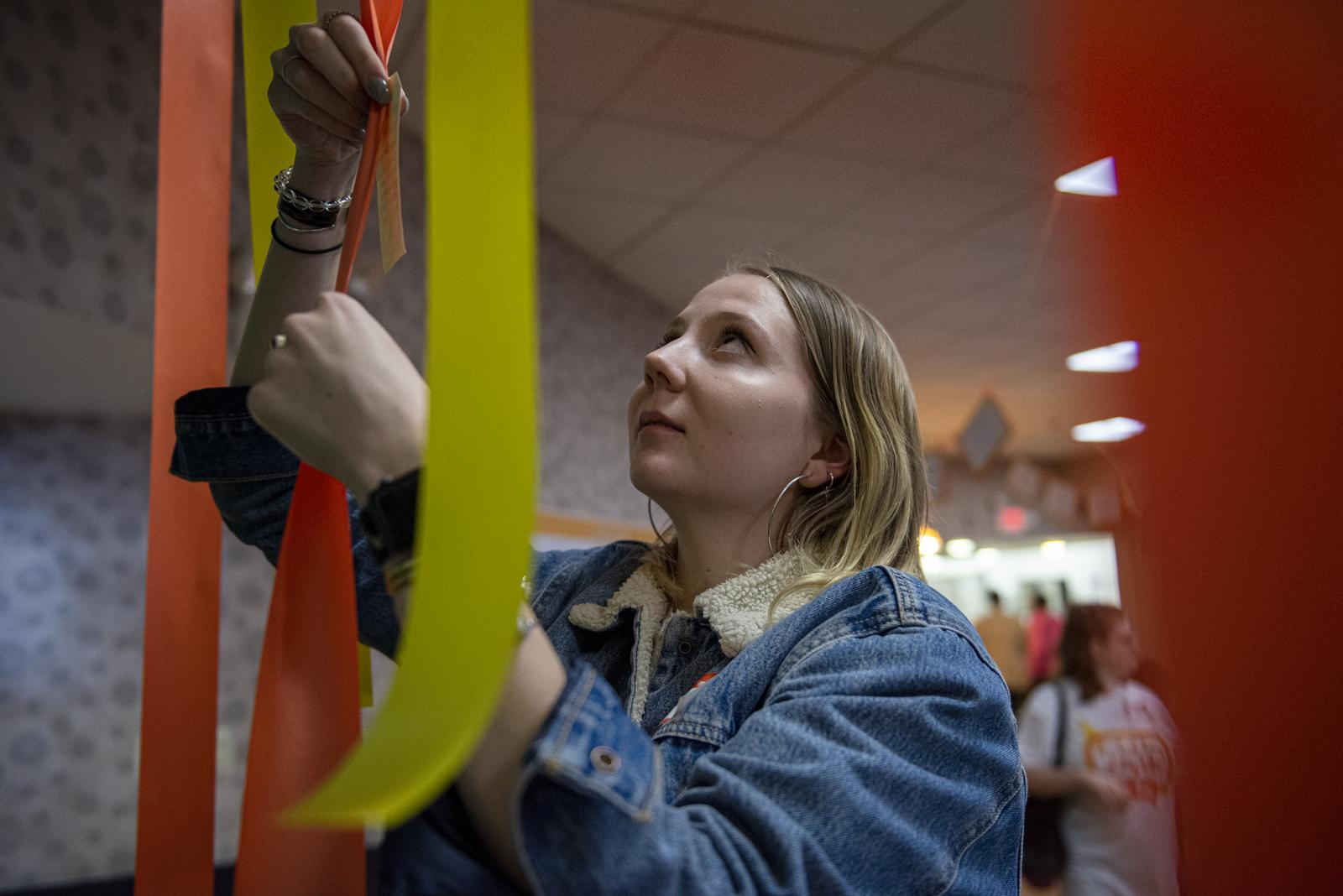 Grace Pfeifer, 21, a student from the College of New Jersey, hangs strips of short stories written from students of her school at the 10th anniversary of Best Day of My Life So Far, on Friday, Nov. 8, 2019, at Philadelphia Senior Center, in Philadelphia, Pa.