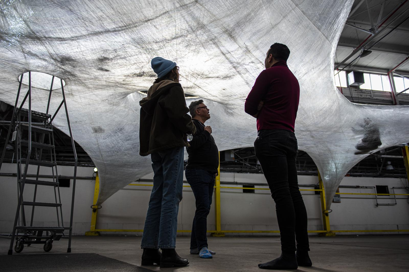 George Alley, right, Matthew Ray, middle, talk with Gina Grasso, a staff from Group X that made the art piece, in the Building 694 at the Navy Yard, in Philadelphia, Pa, on Sat, Nov. 9, 2019.