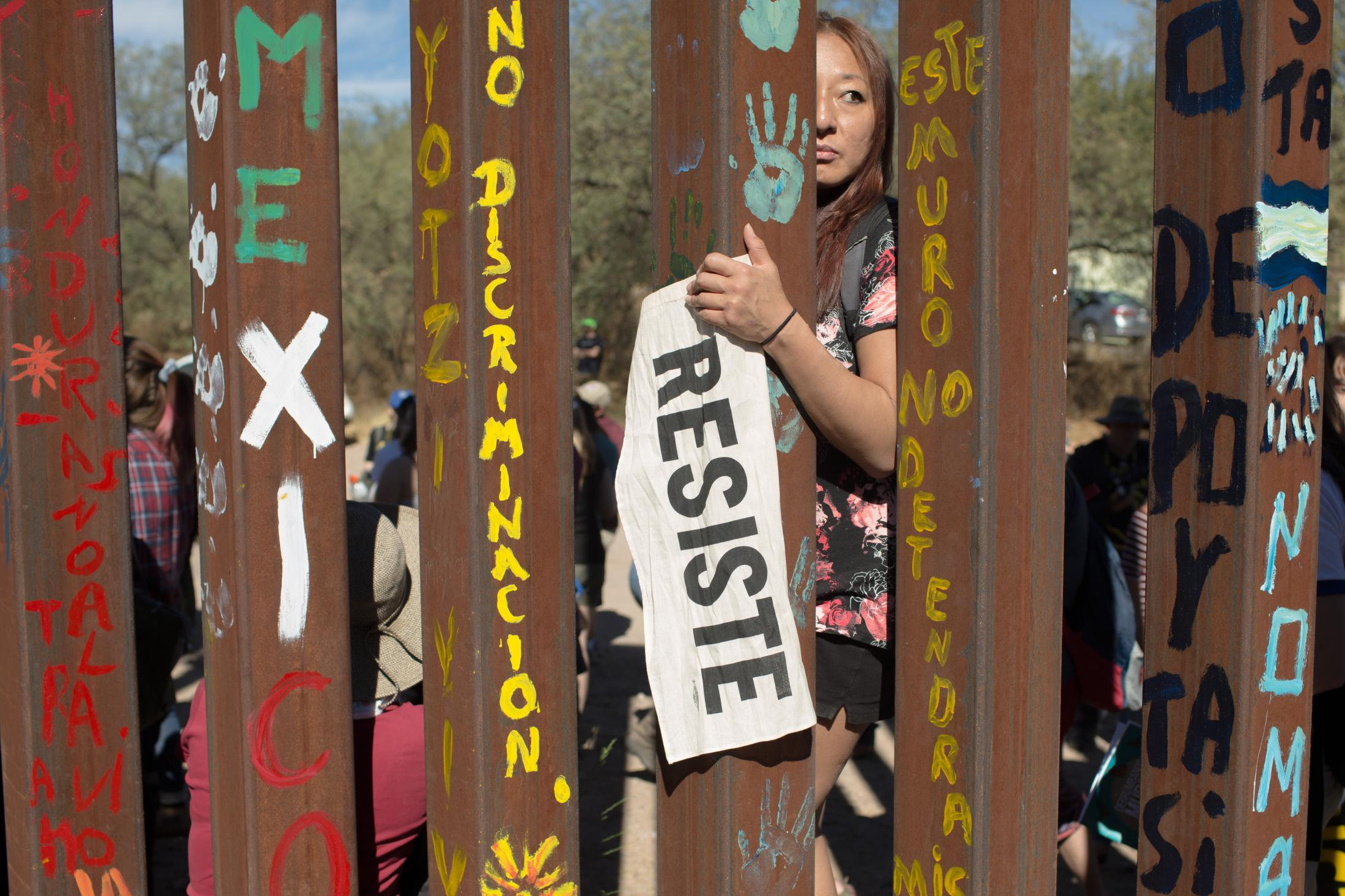 A protester holding a sign that says resist in Spanish stands on the United States side of the border wall that separates Nogales, Sonora and Nogales, Arizona during the SOA Watch Border Encuentro 2017 on November 11, 2017.