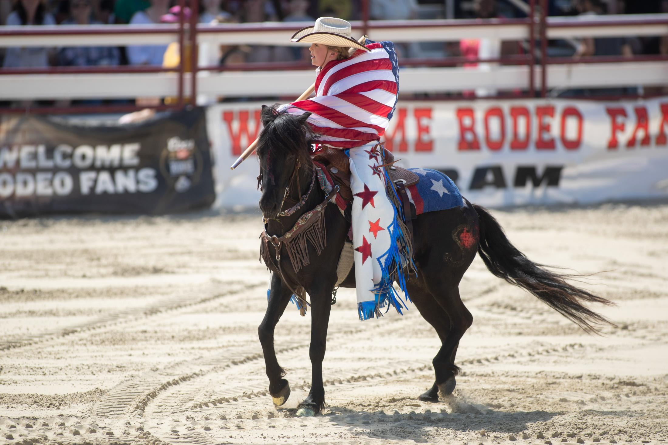 The wind wraps an American Flag around Shyla O'Neill during a tribute to veterans at the Goshen Stampede before the kids rodeo on Saturday afternoon June 15, 2019, in Goshen, CT.