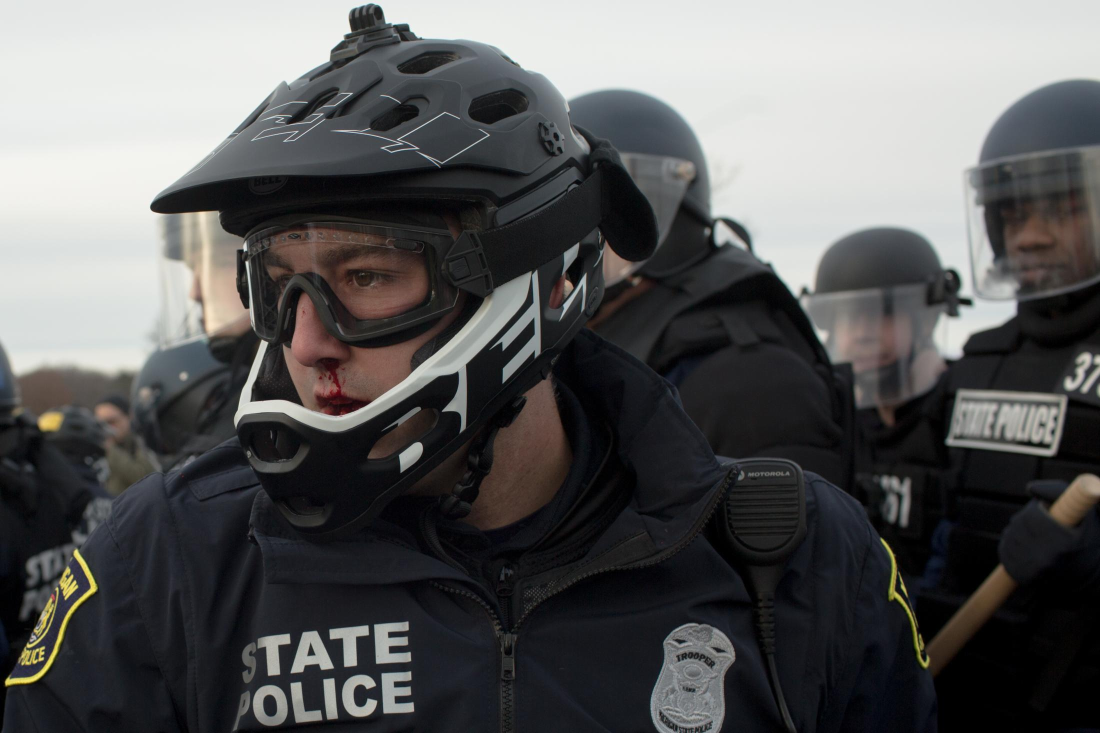 A Michigan State Police Officer with a bloody nose uses his bike to move protesters back outside of the venue that Richard Spencer was scheduled to speak at on the campus of Michigan State University near East Lansing, MI on March 5, 2018.