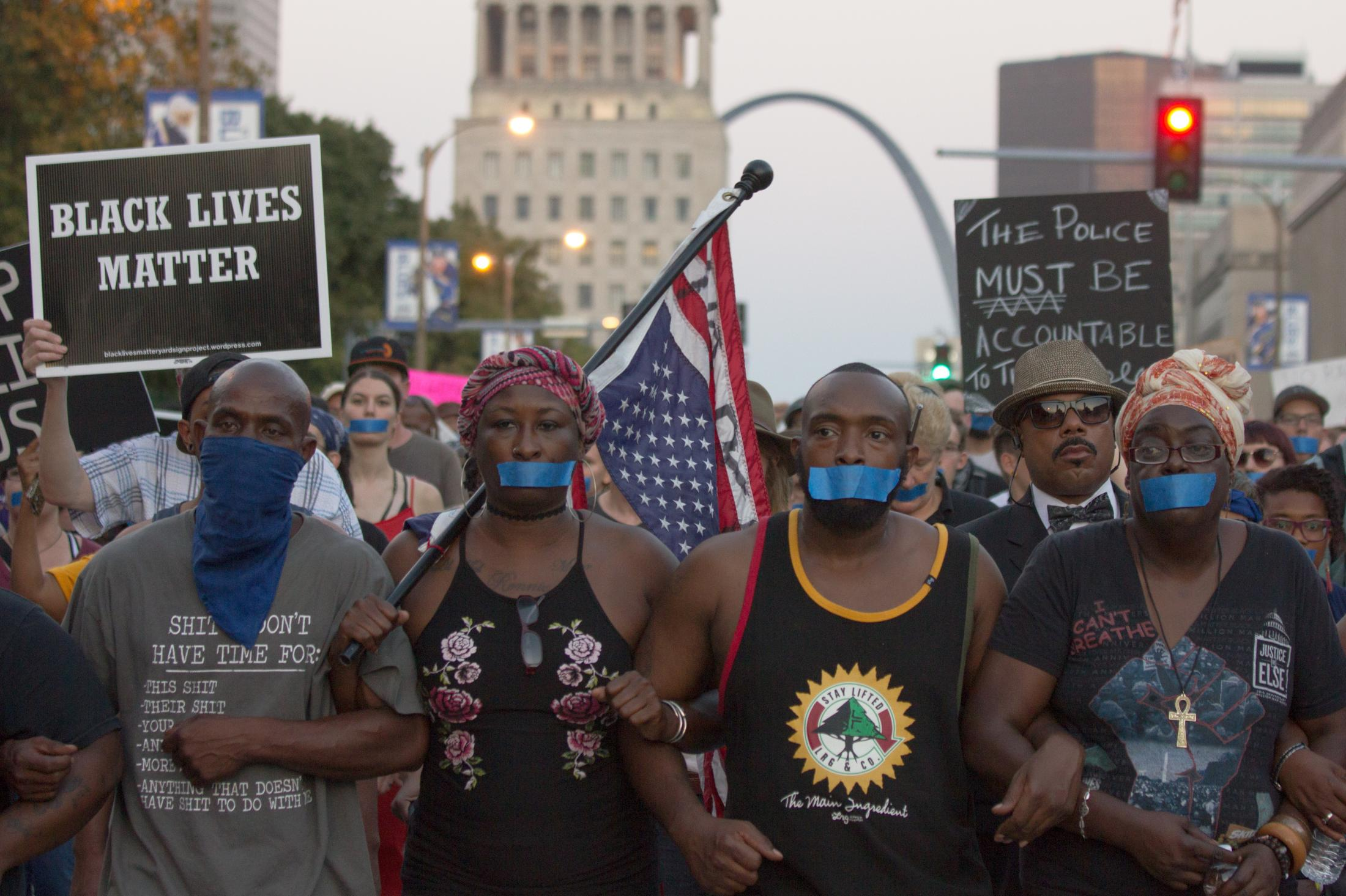 Protesters march down Market Street toward the St. Louis City Police Headquarters with blue tape over their mouths during a blue silence is violence demonstration on September 25, 2017 in St. Louis, MO.