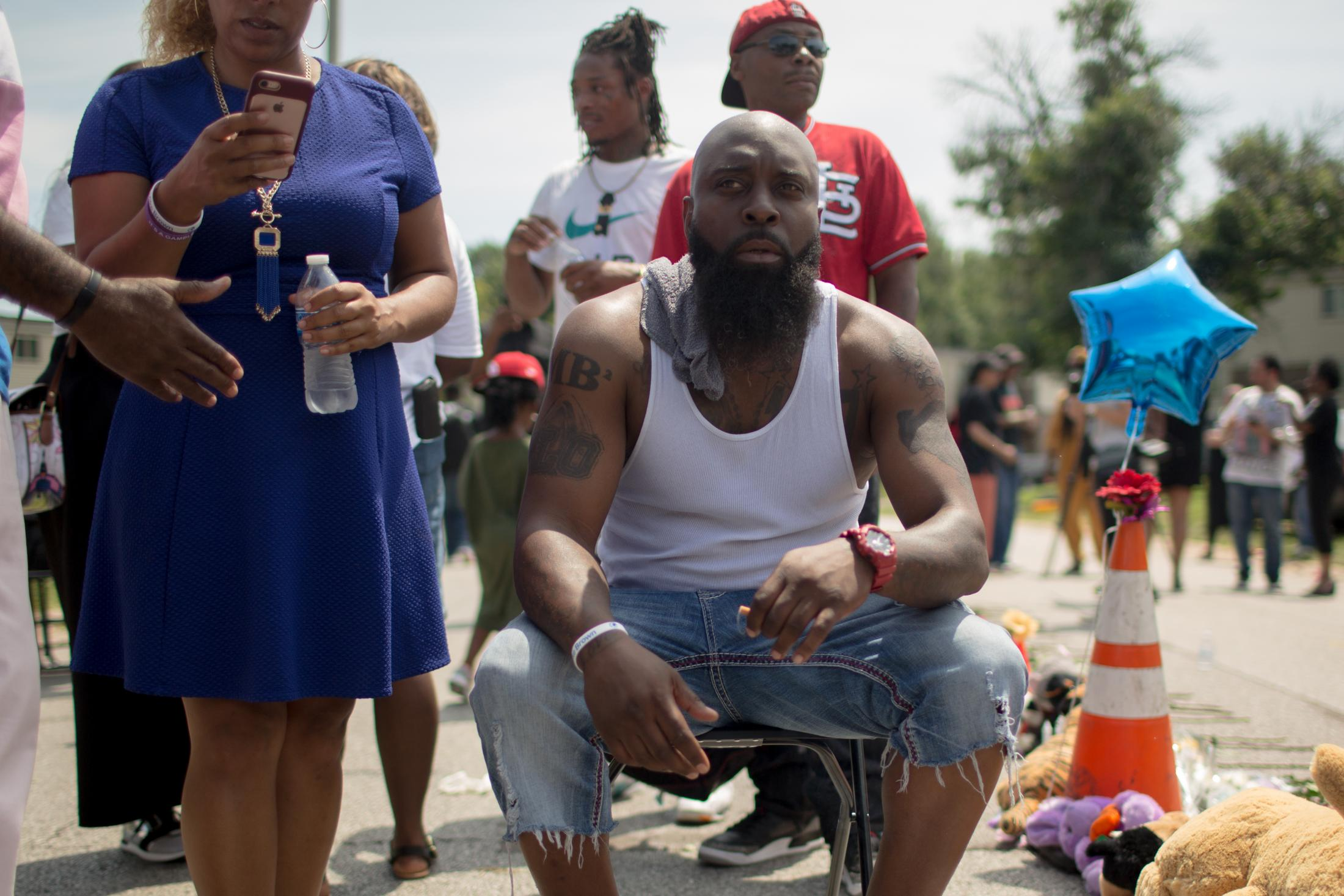 Michael Brown Sr. sits next to a memorial placed for 5th annual Michael Brown Memorial Service at the Canfield Green apartment complex in Ferguson on Friday, May 9, 2019.