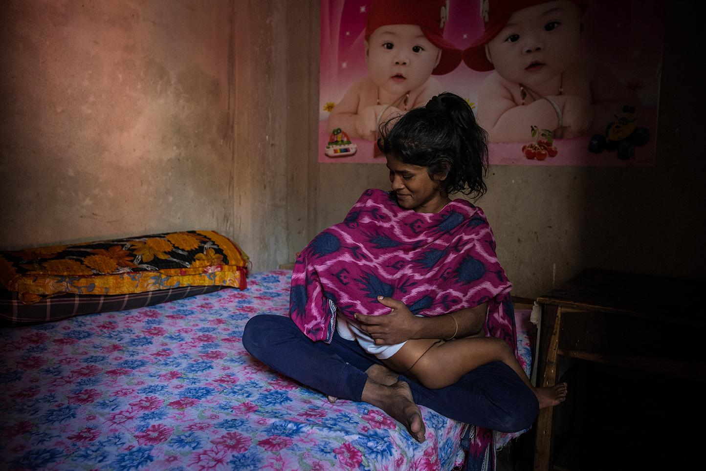 Tania, 15, with her son Thangil, 2, is a sex worker in Daulatadia Brothel in Daulatadia, Rajbari, Bangladesh. She is not sure who the father is, but it is a client. Daulatadia is considered one of the largest brothels in the world and serves roughly 2500-3000 men daily. Bangladesh is the only Muslim country in the world where prostitution is legal. Though legally prostitutes must be at least 18 years of age many are tricked into the profession at a very young age.