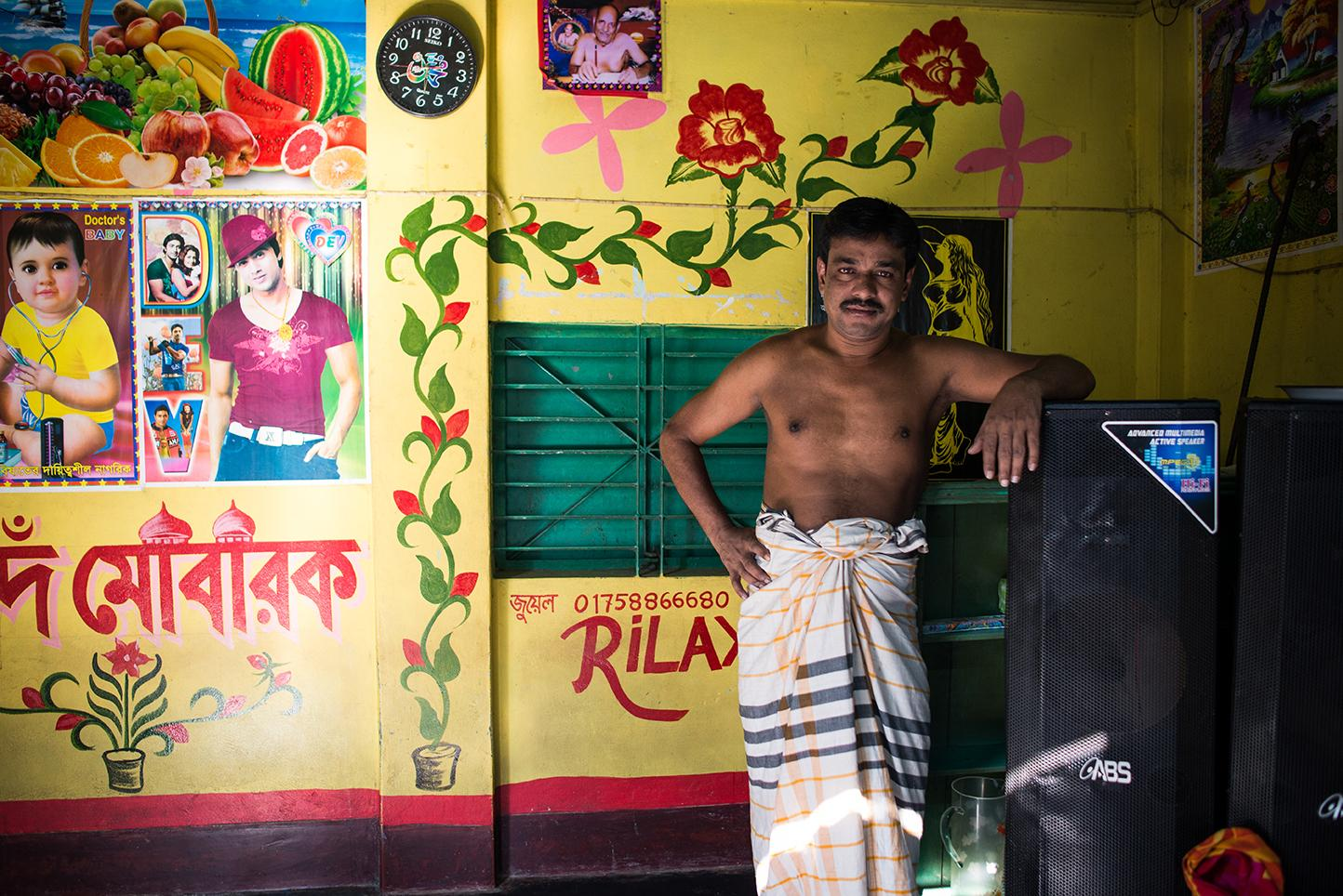Dulal, 40, from Pabna village in Bangladesh proudly rests on the speakers at his nightclub, where he acts as club DJ. He has been running the club for six months. Men come to the club and drink alcohol and buy private dances from the sex workers. Daulatadia Brothel in Daulatadia, Rajbari, Bangladesh. Daulatadia is considered one of the largest brothels in the world and serves roughly 2500-3000 men daily. Bangladesh is the only Muslim country in the world where prostitution is legal. Though legally prostitutes must be at least 18 years of age many are tricked into the profession at a very young age.